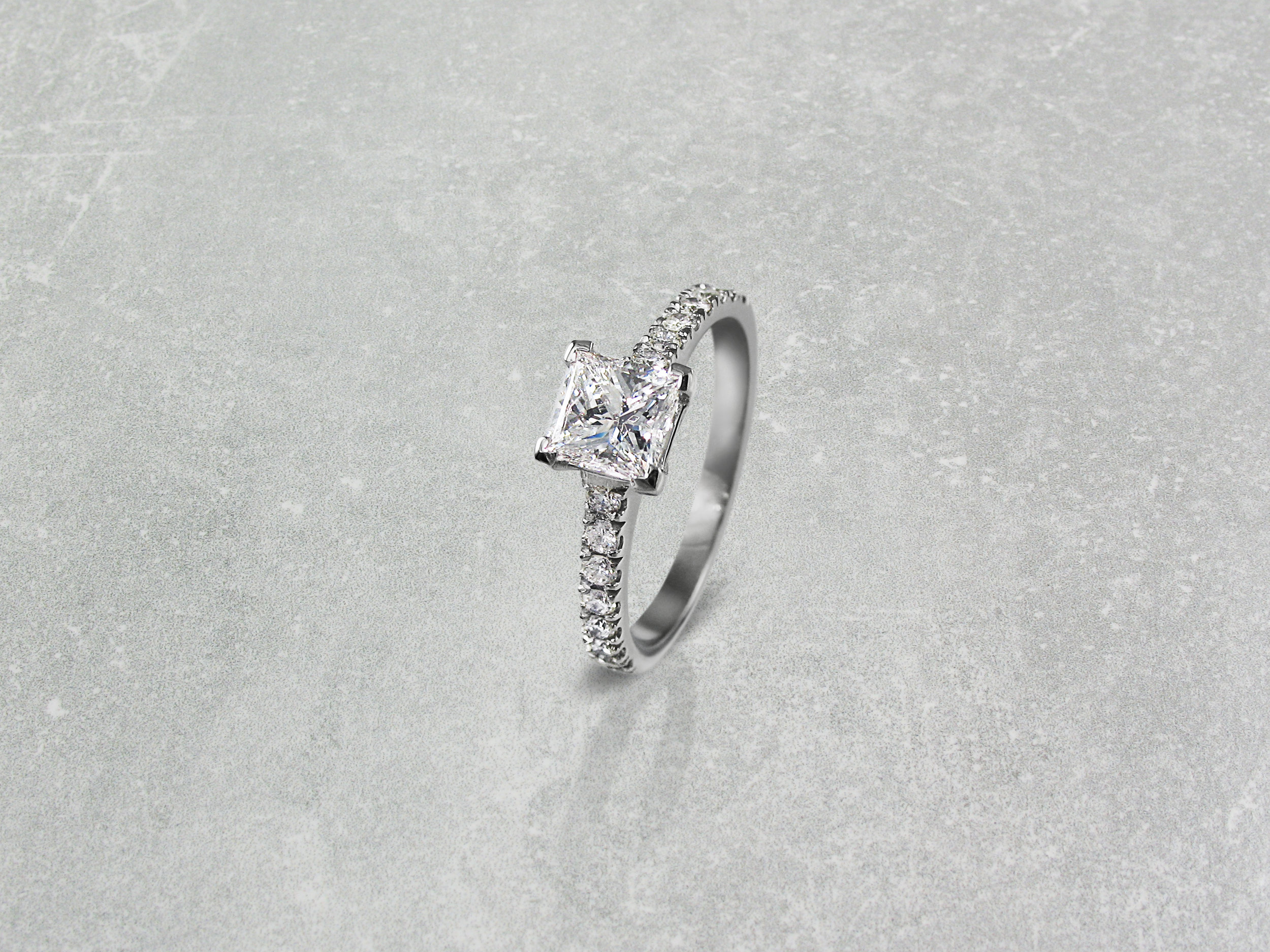 Princess cut diamond four claw engagement ring with diamond band