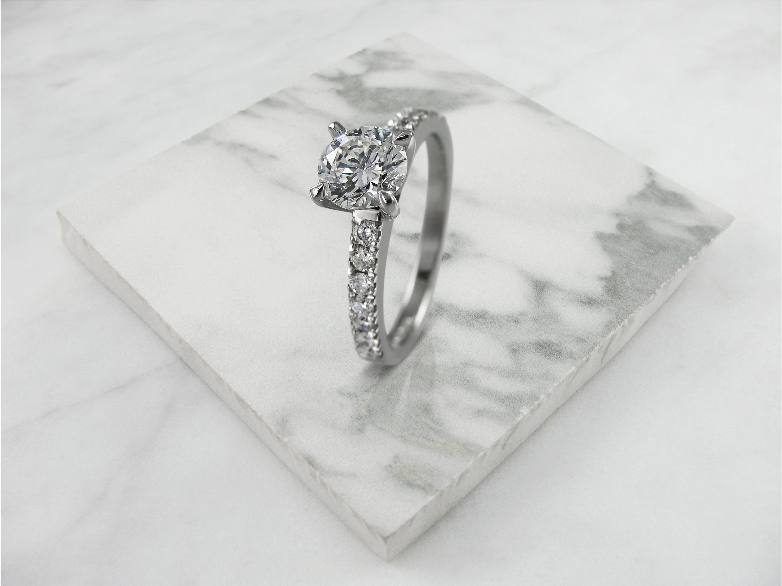 Round brilliant cut diamond four claw engagement ring with diamond band