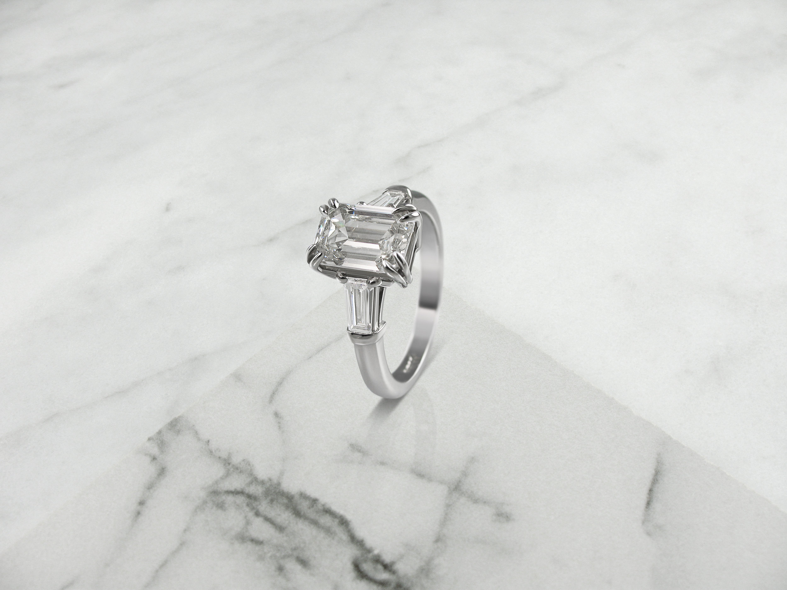 Emerald cut diamond and tapered baguette engagement ring