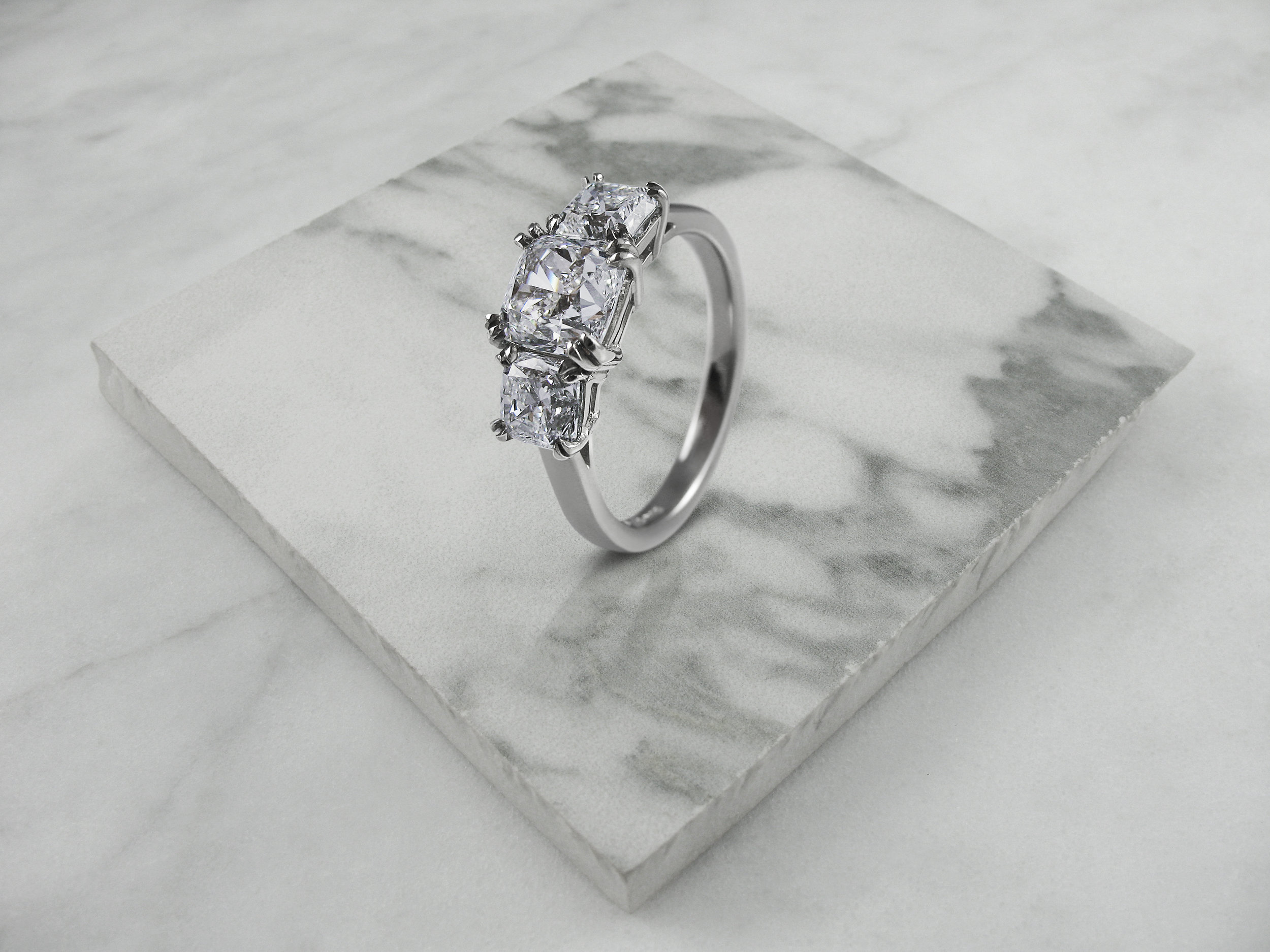 Cushion cut diamond trilogy engagement ring
