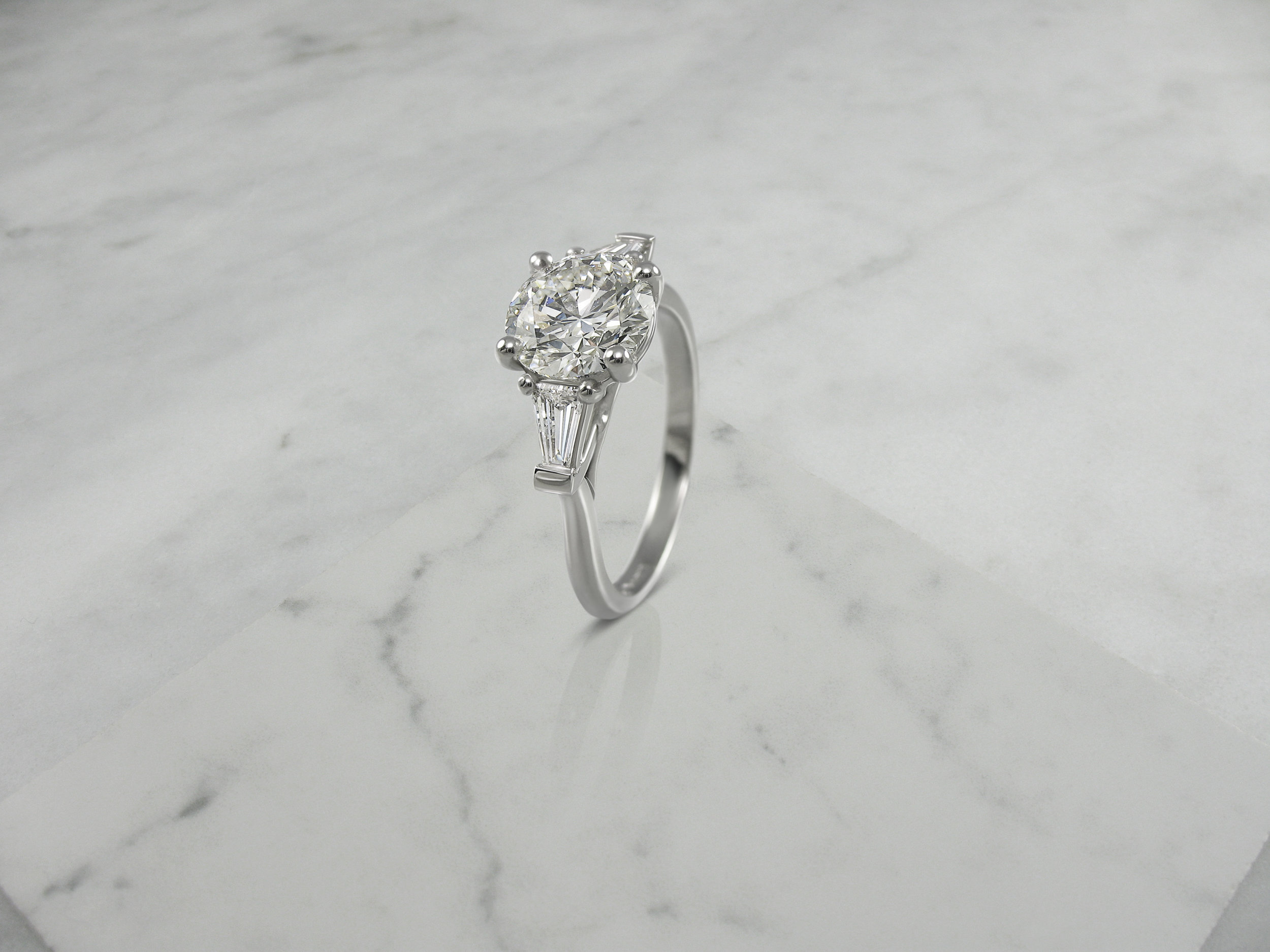 Round brilliant cut diamond and tapered baguette engagement ring