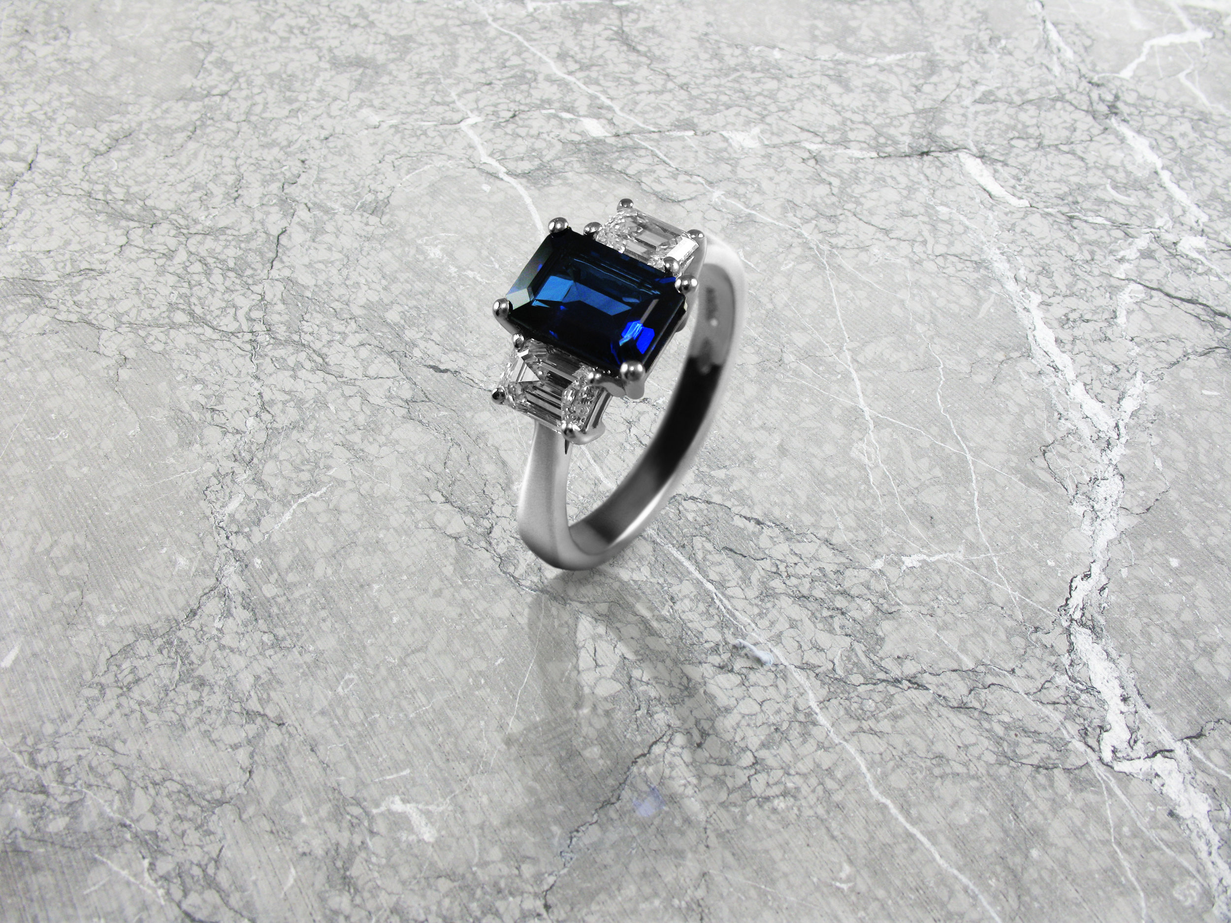 Emerald cut sapphire and diamond trilogy engagement ring