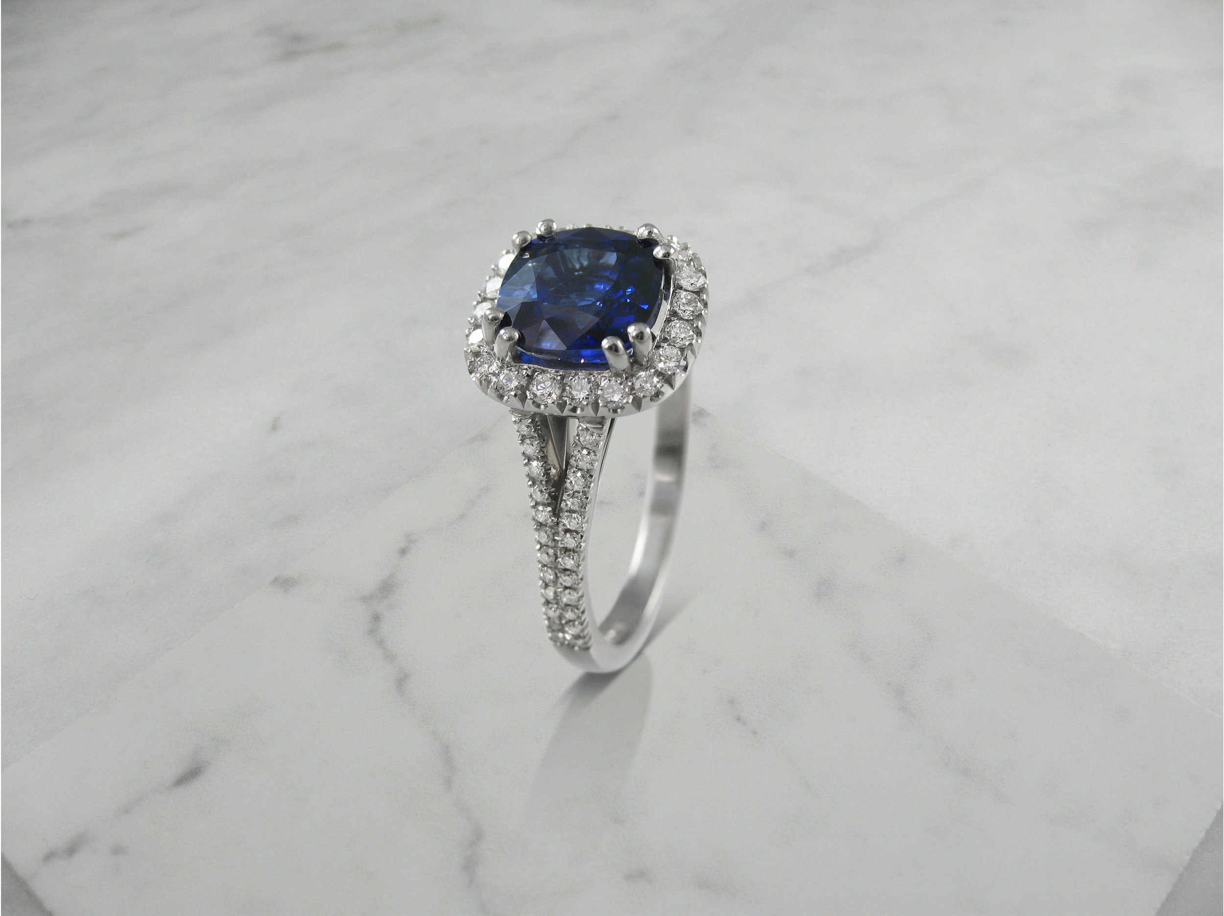 Cushion shaped sapphire and diamond halo engagement ring with split diamond band