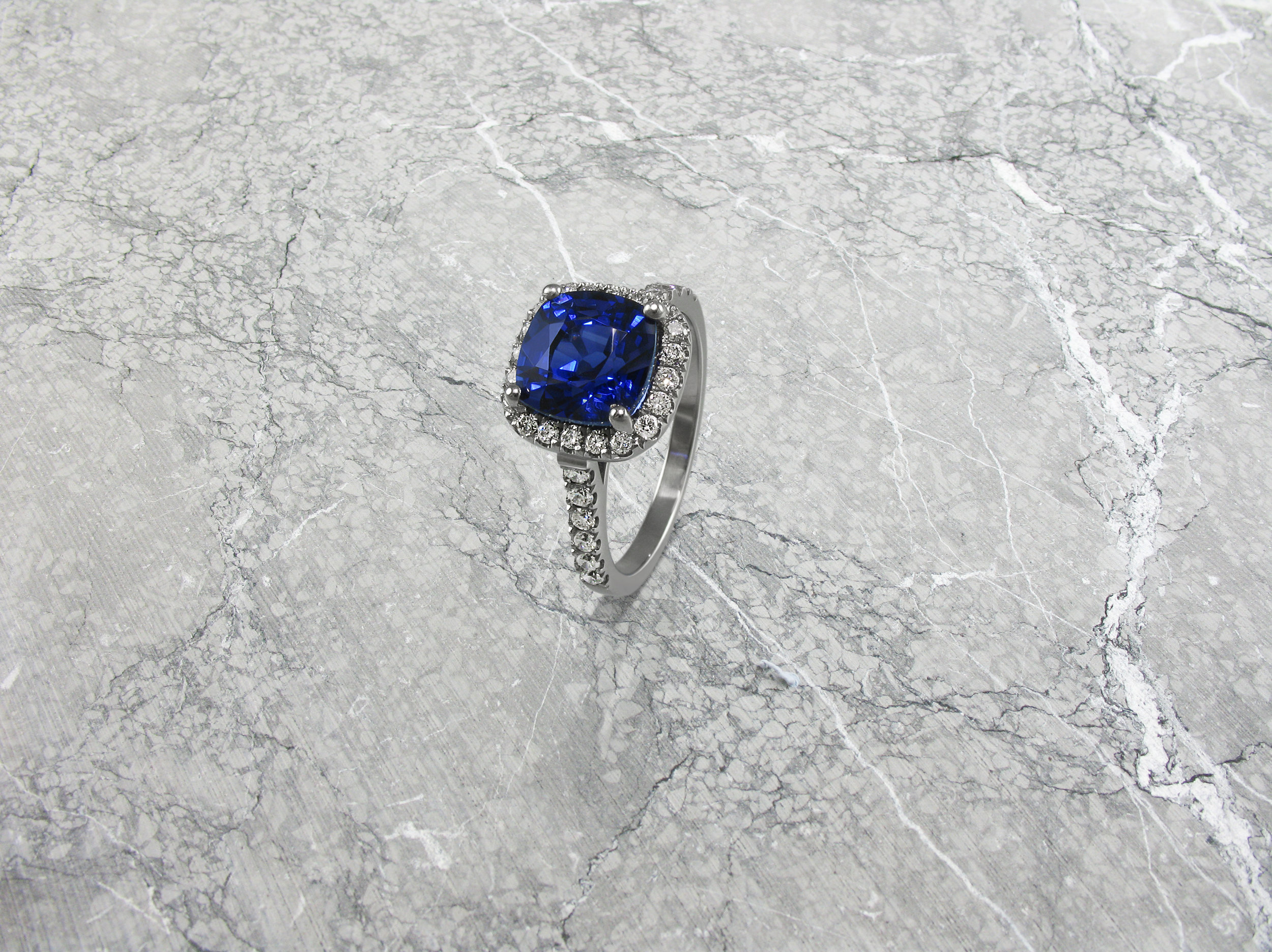 Cushion shaped sapphire and diamond halo engagement ring