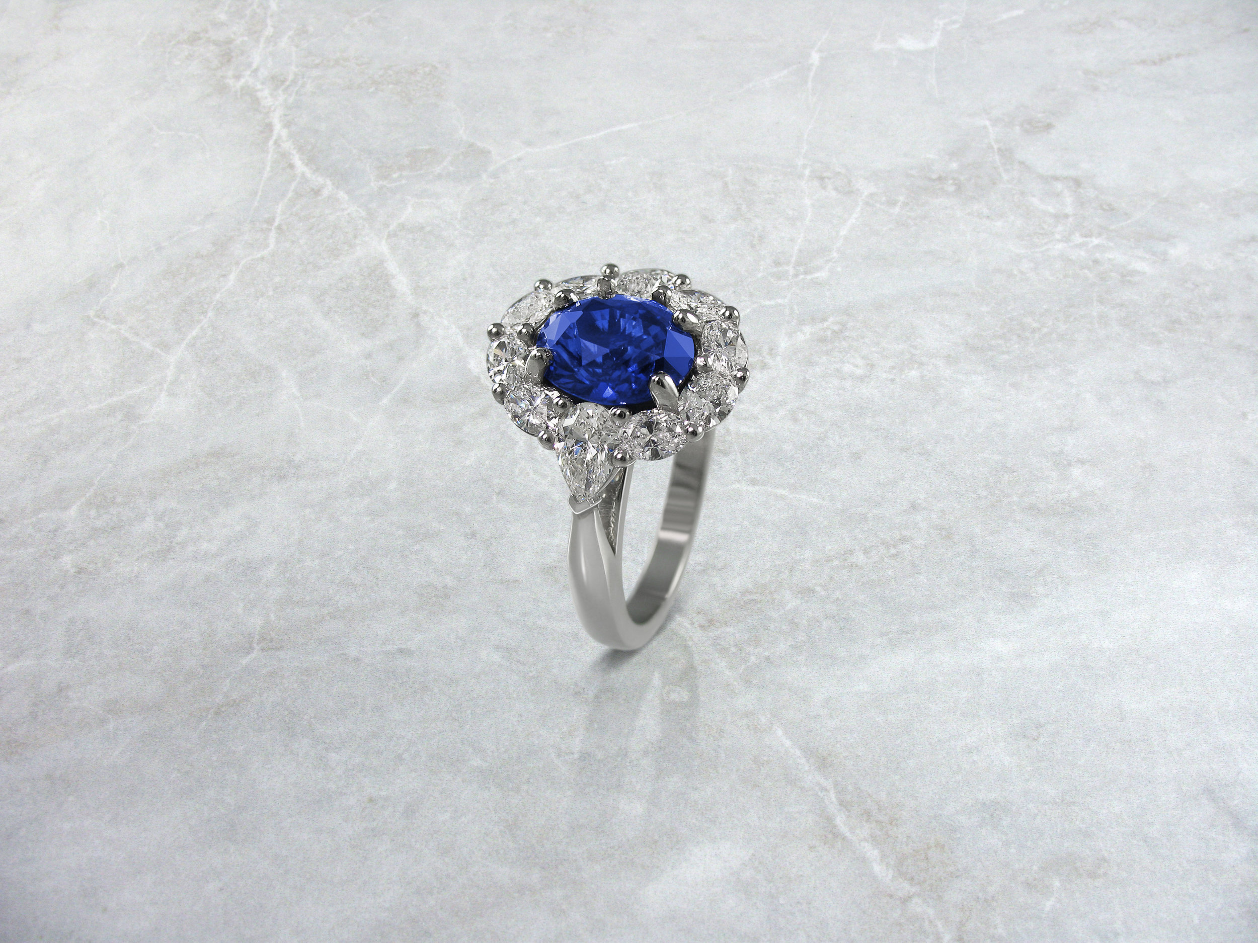 Oval sapphire and diamond cluster engagement ring with pear shaped side diamonds