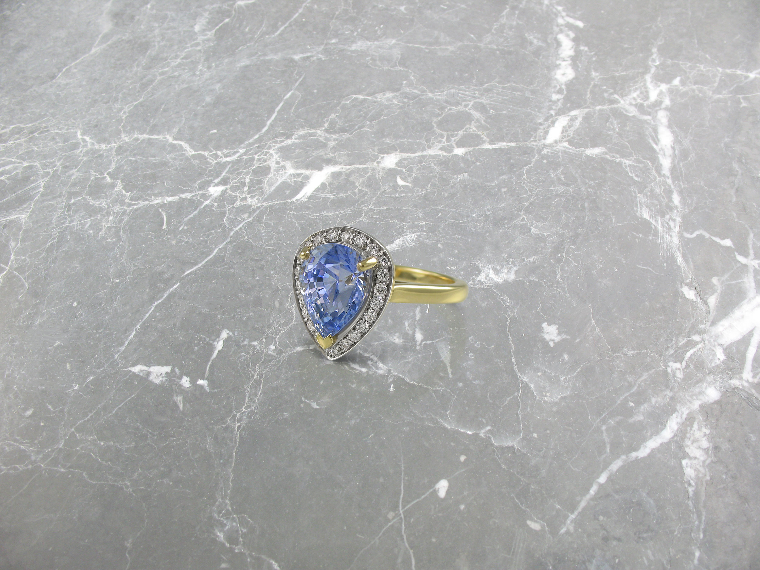 Pear shaped sapphire and diamond yellow gold halo engagement ring