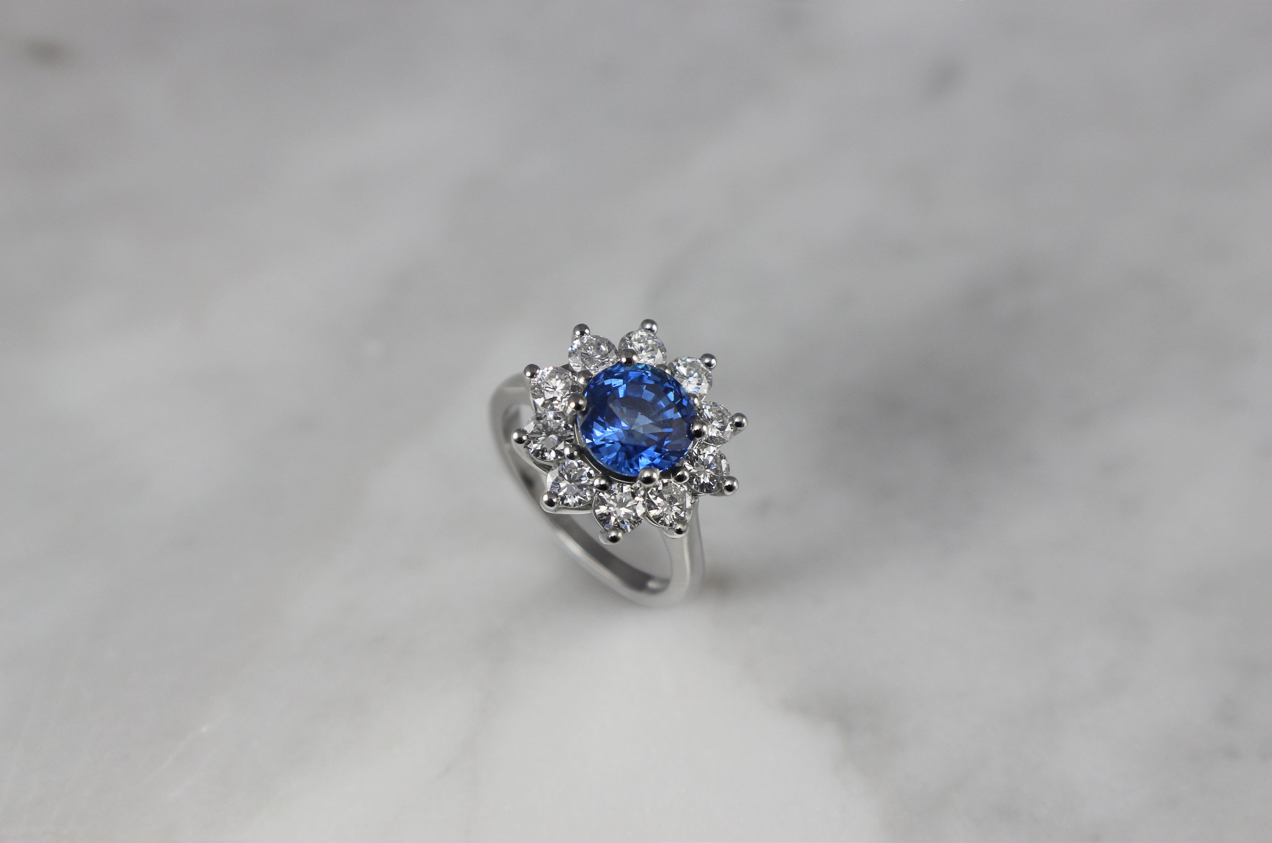 Round sapphire and diamond cluster engagement ring