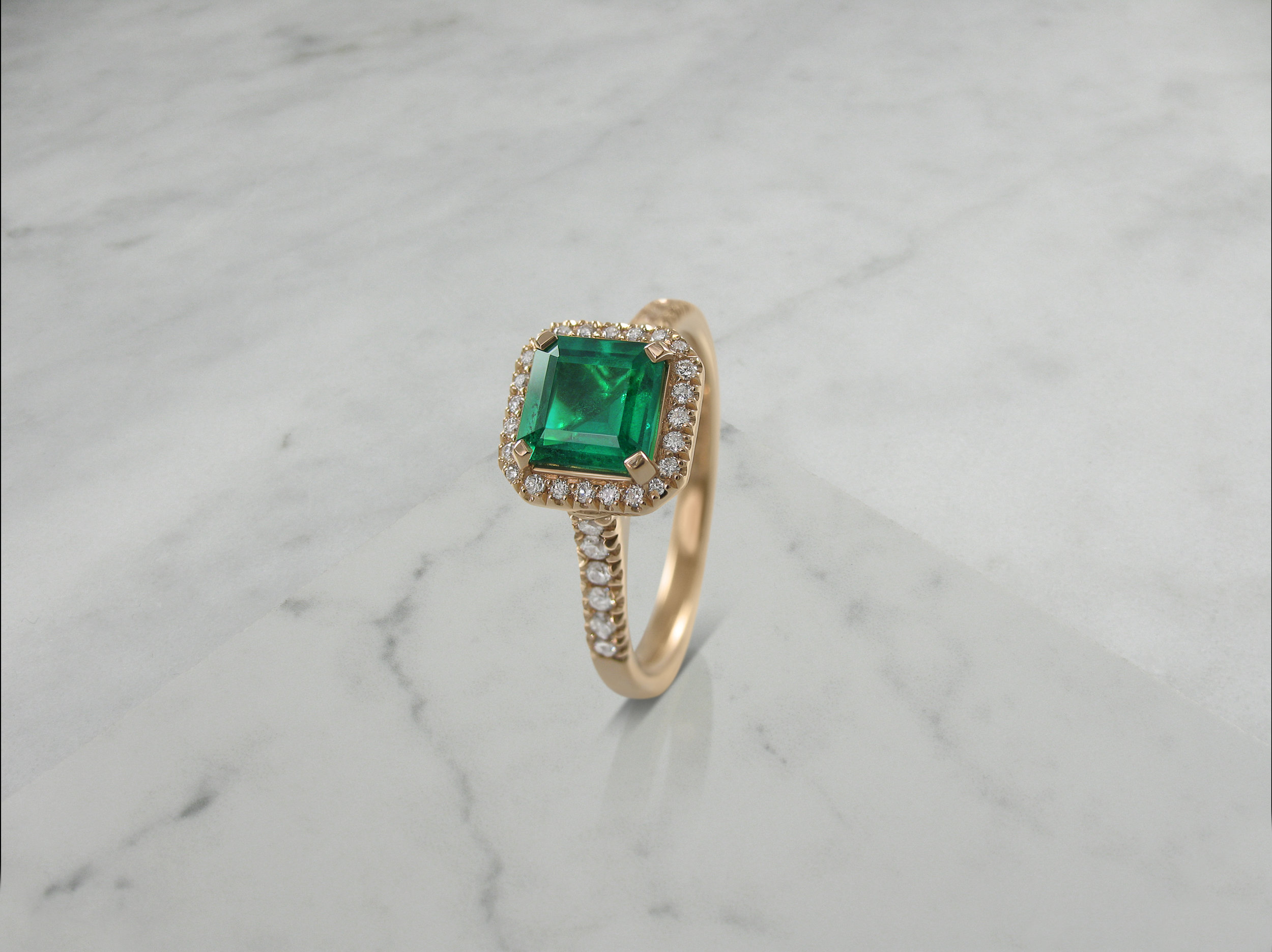 Emerald and diamond rose gold halo engagement ring