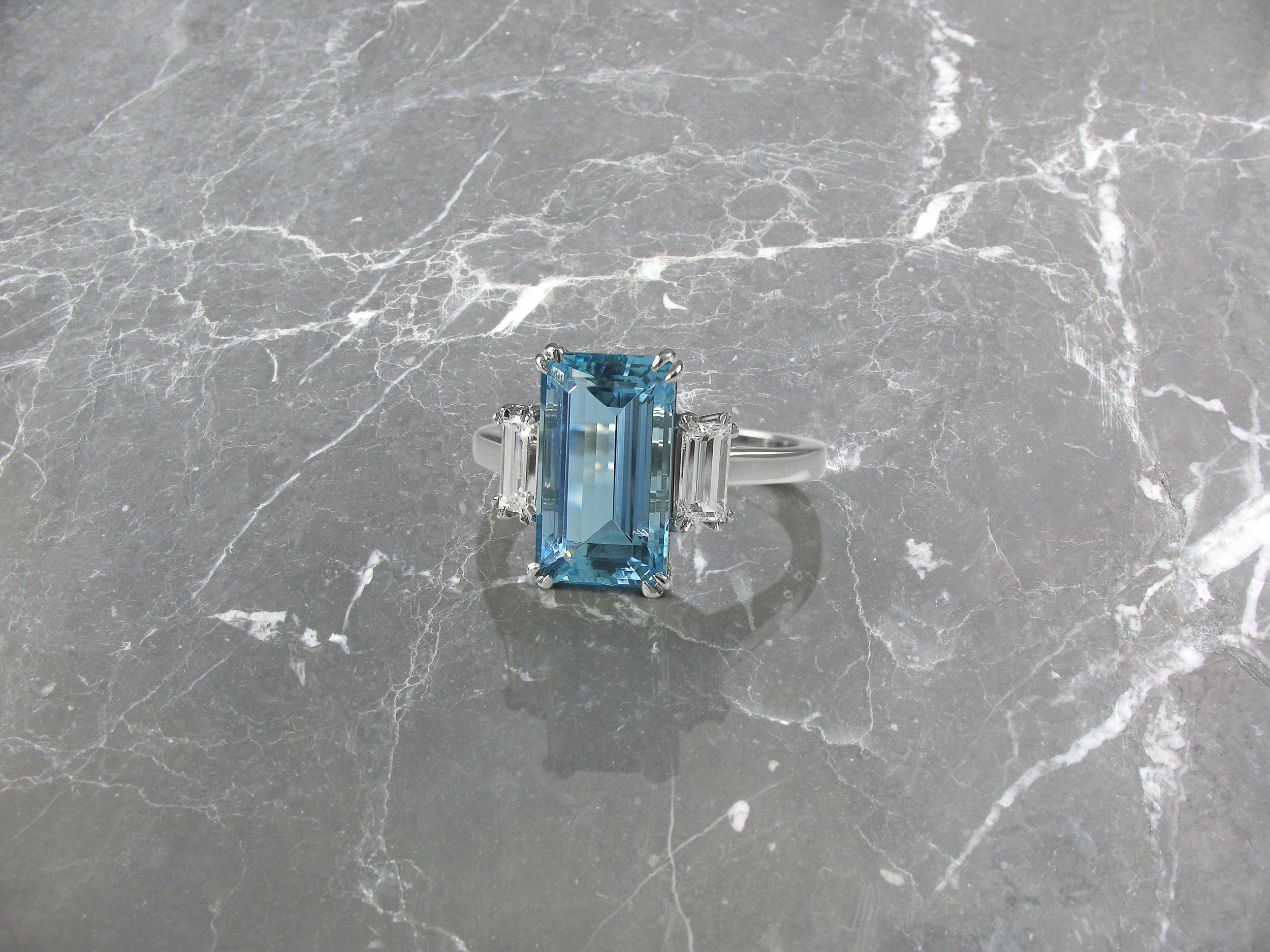 Emerald cut aquamarine and diamond trilogy engagement ring