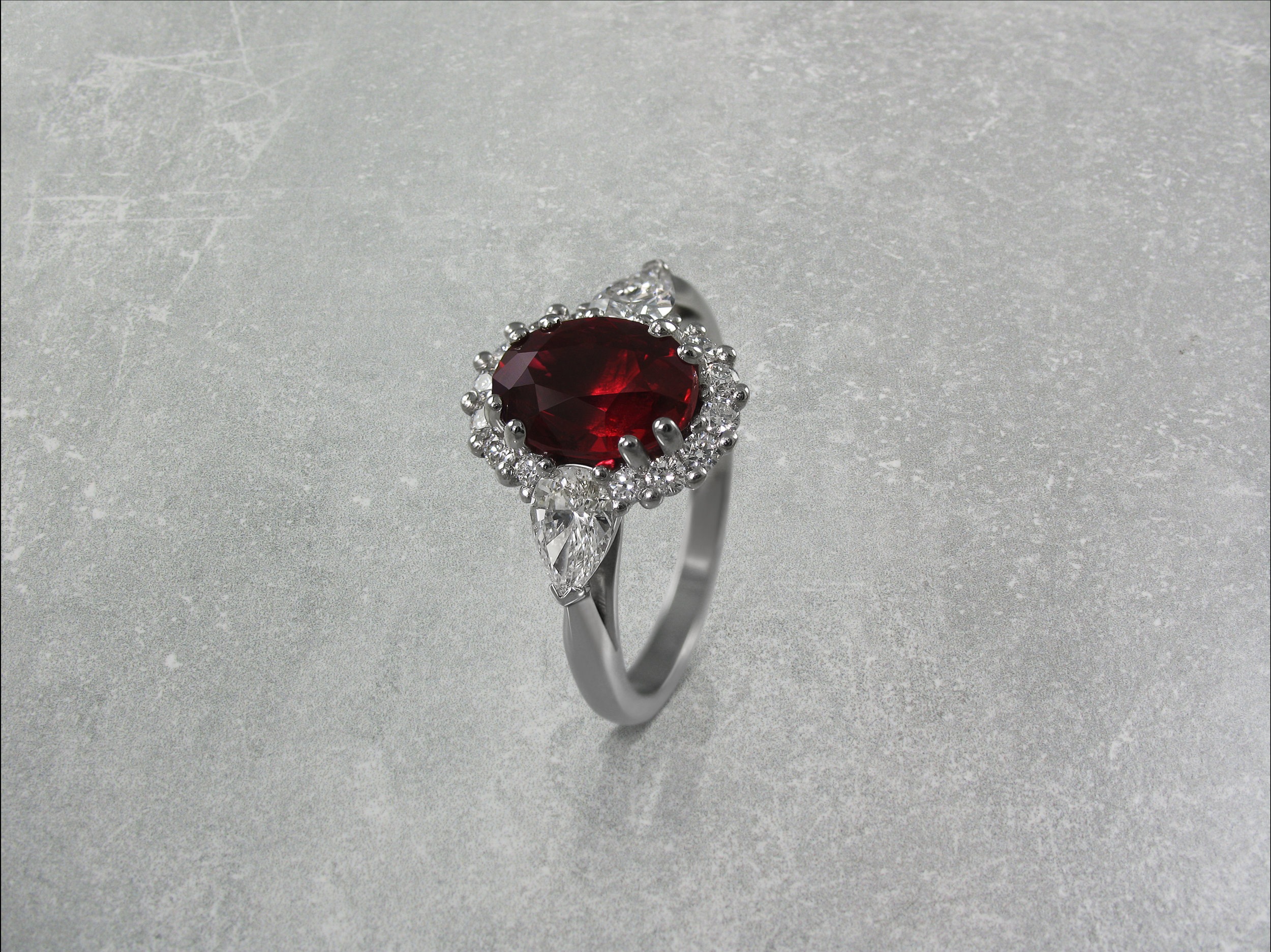 Oval ruby and diamond cluster engagement ring with pear shaped diamond shoulders