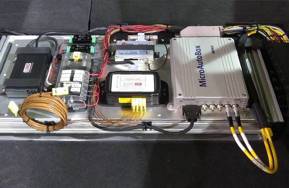 The dSPACE MicroAutoBox with additional electronic modules installed in the trunk of Chevrolet Volt.