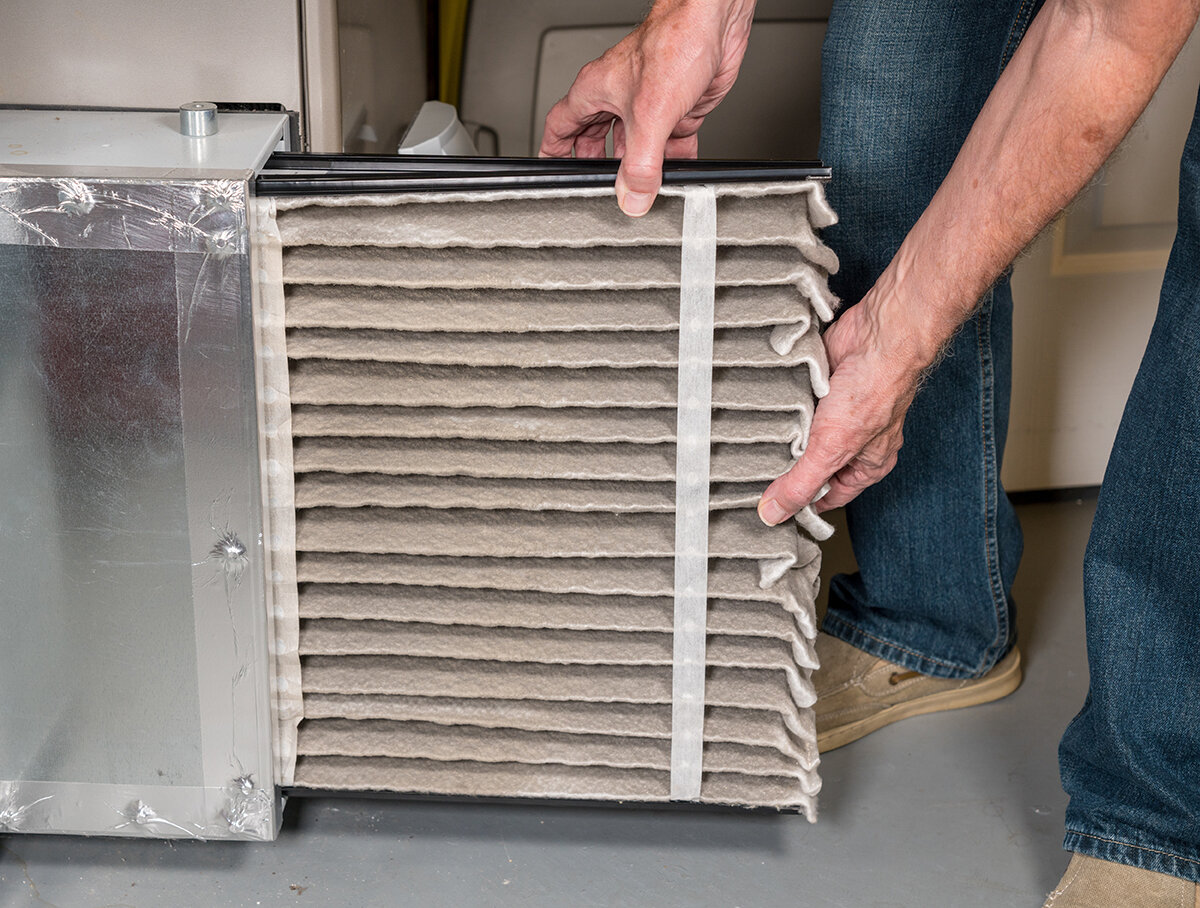 Changing out a dirty air filter on a furnace.