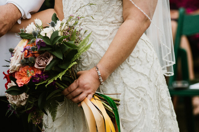 Satin and velvet ribbons in varying shades adorn the bride's autumnal bouquet.