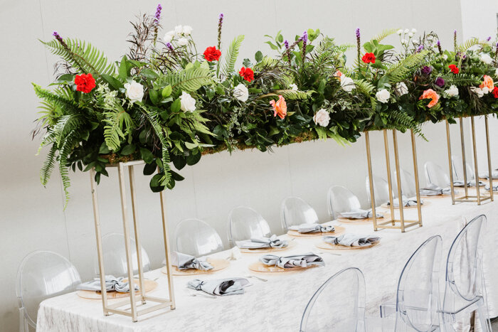 A closer look at the head table's colorful combination of peach & white roses, Liatris, and deep purple & red carnations thoughtfully placed among an overflowing bouquet of greenery is reminiscent of a lush botanical garden.