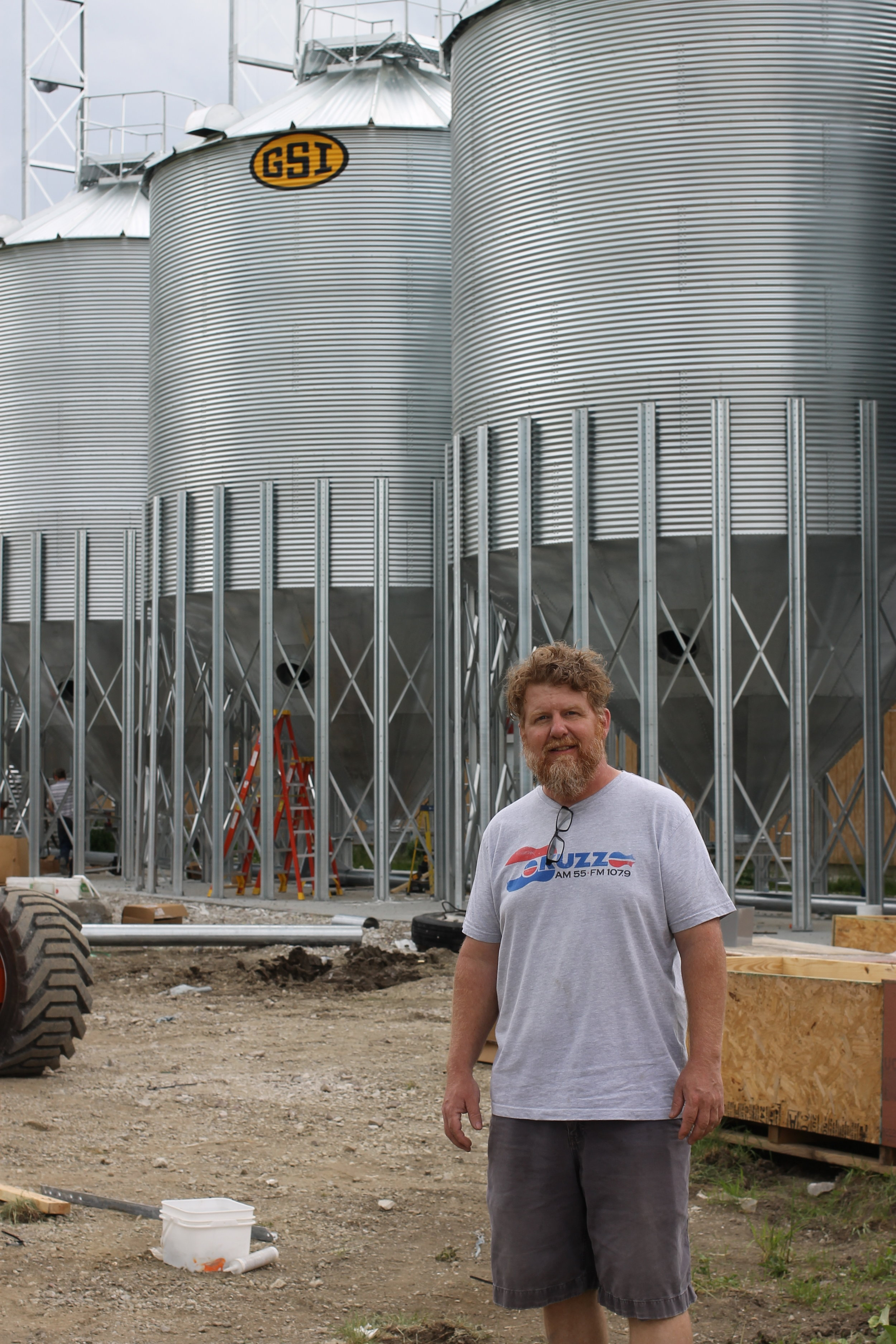 Andrew Peterson co-owns Nordic Farms. The silos behind him hold grain for malting.