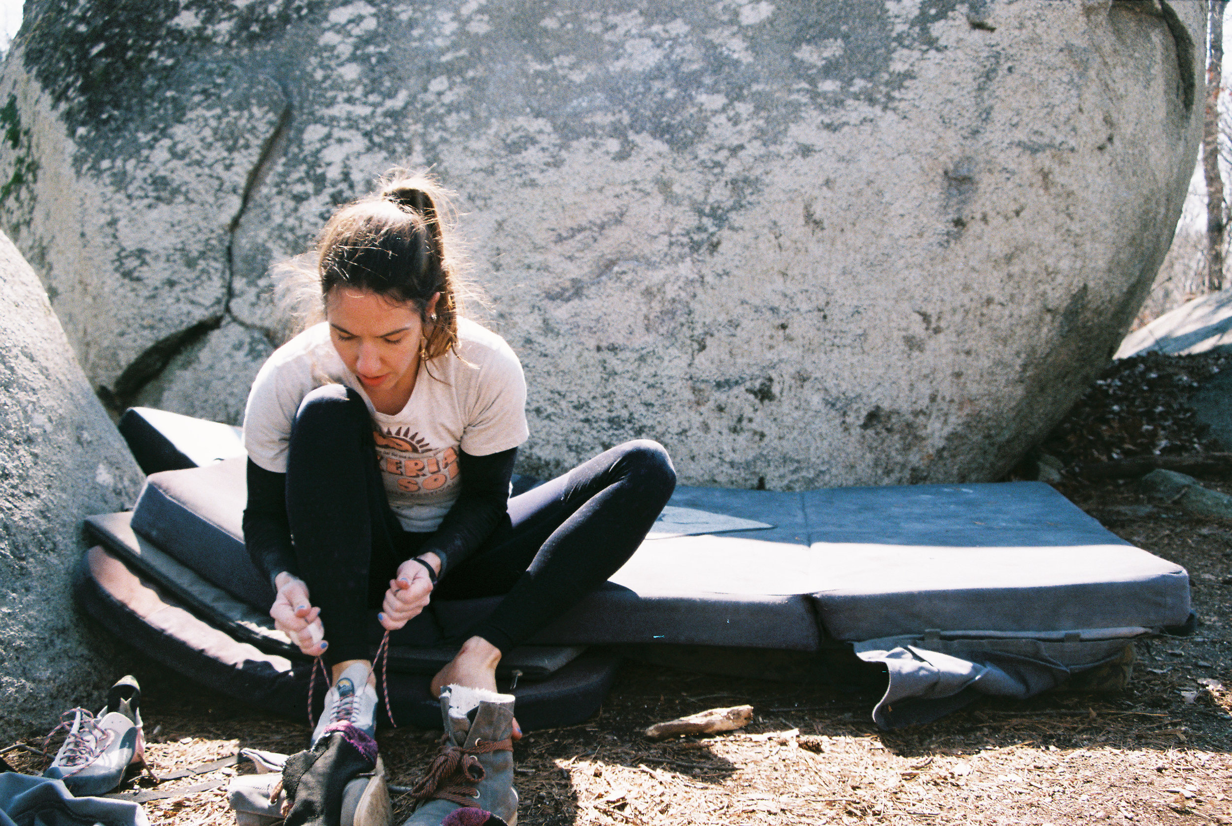 rock climber tightening shoes