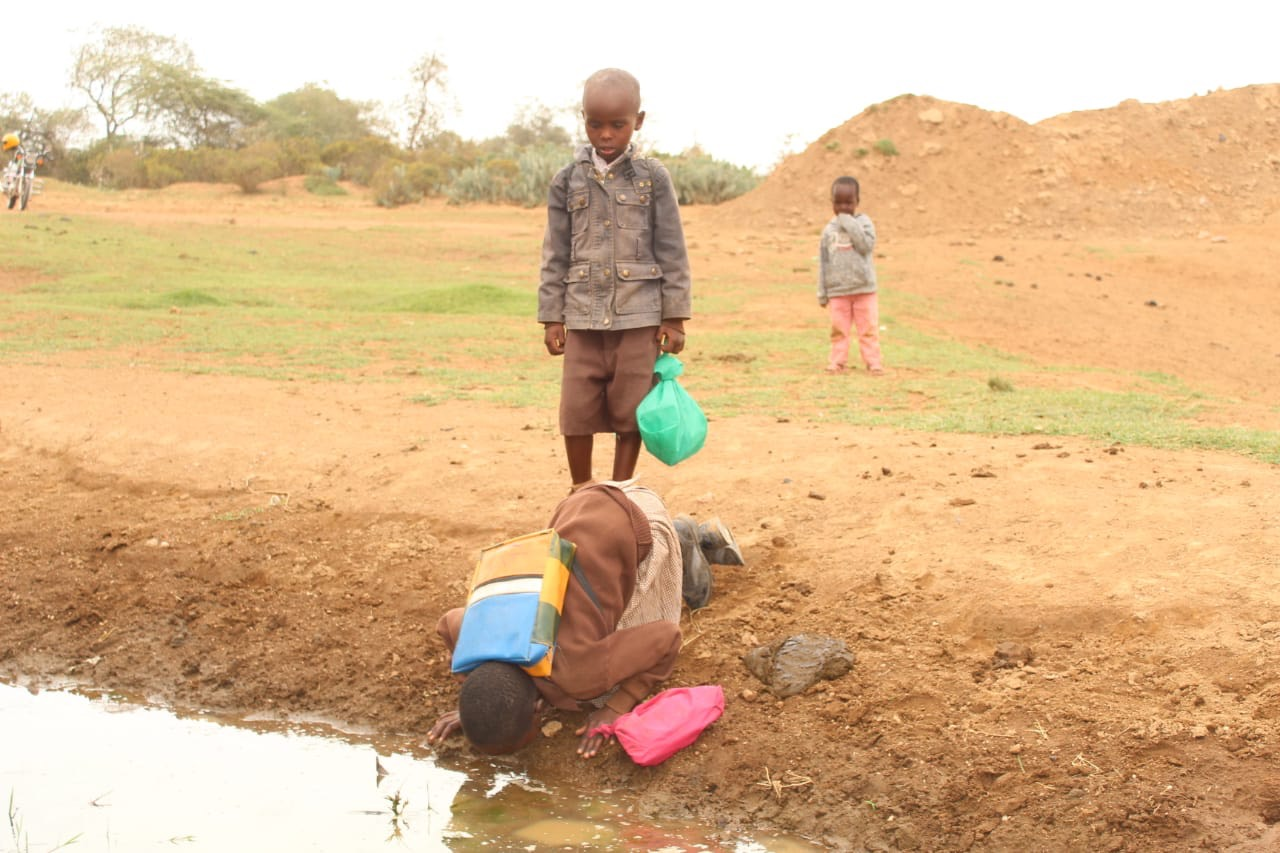School children quench their thirst with dirty water.