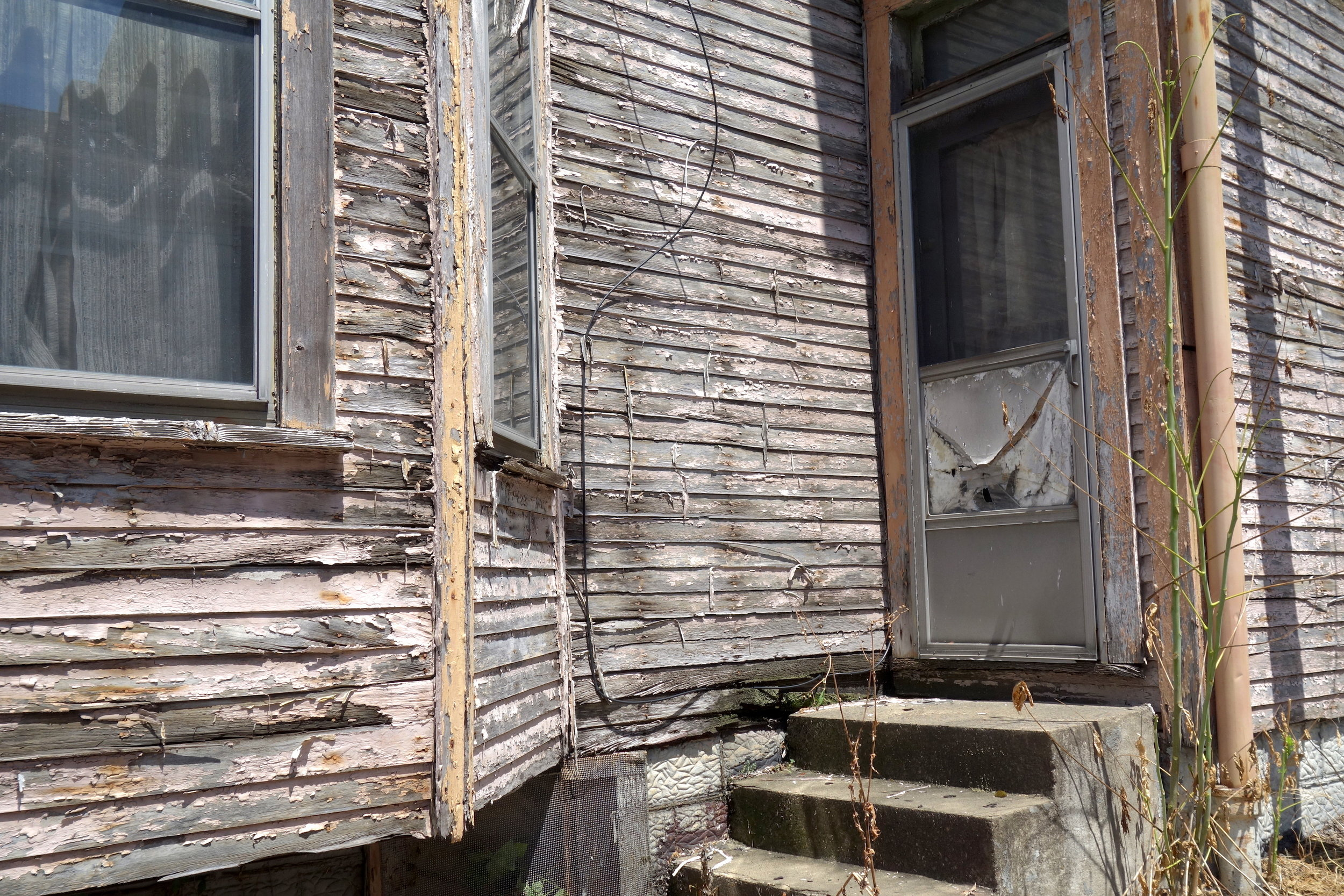 Figure 22. Side entrance to a weather-beaten house in South Wheeling, 2016. Photograph by Joseph Heathcott.