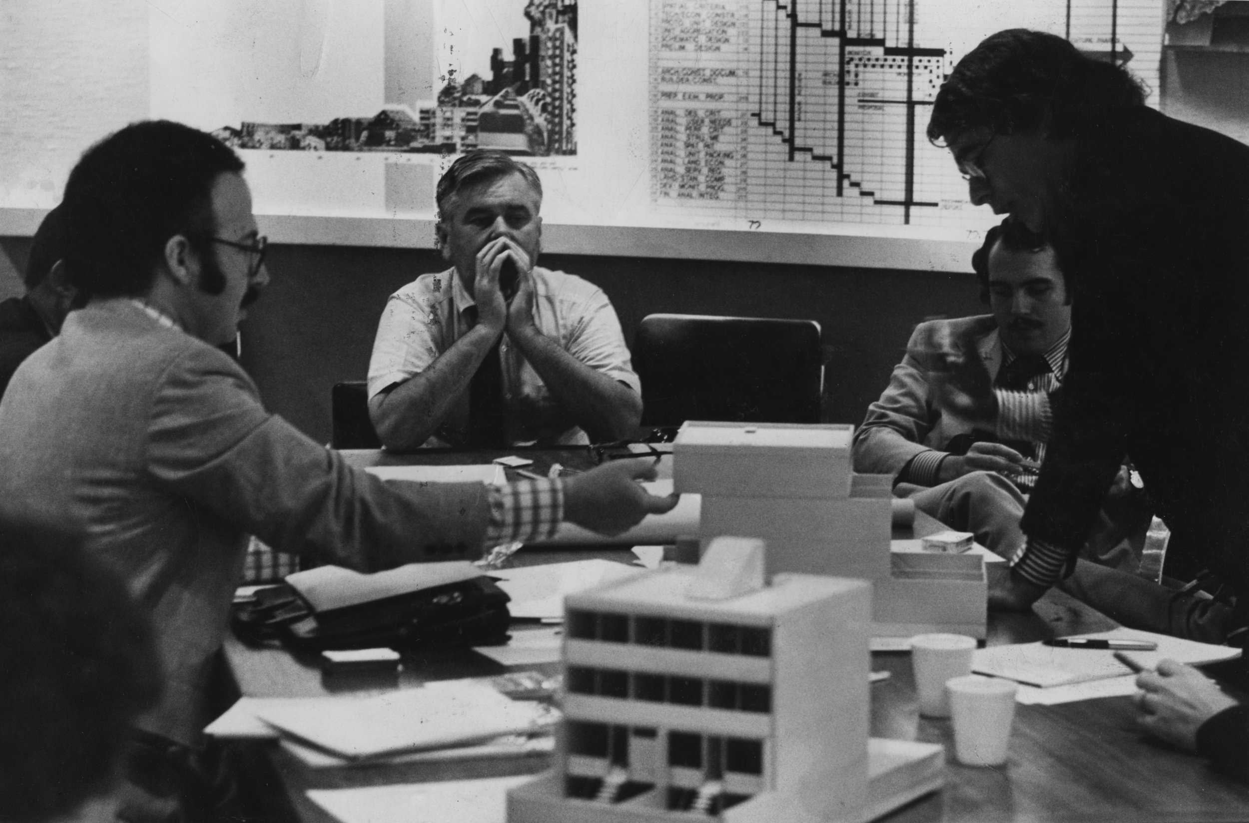 Figure 2. Marcus Garvey Park Village planning meeting, 1972. Ed Logue (center) is discussing the ideal housing prototype with chief UDC architect Ted Liebman (left) and architects Tony Pangaro (next to Logue) and Peter Eisenman (farther right). Courtesy of Robert Perron Photography.
