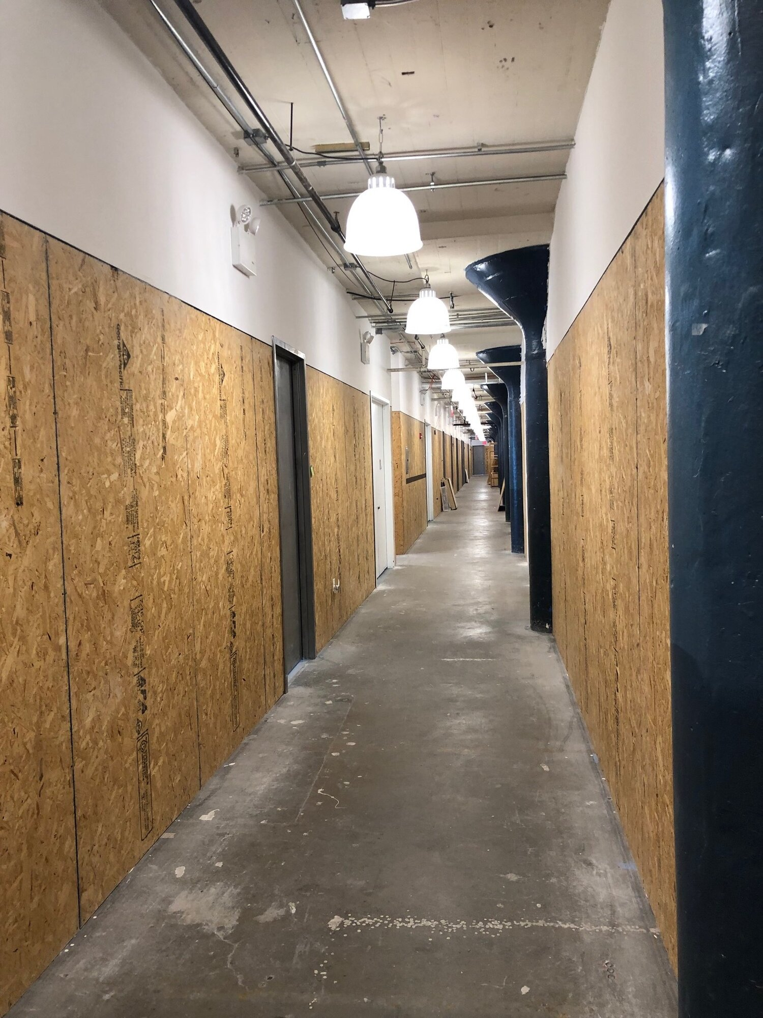 Figure 5. View of the hallway leading to artists' rented studio in Building B, Brooklyn Army Terminal, February 2019. Photo by Mira Rai Waits.