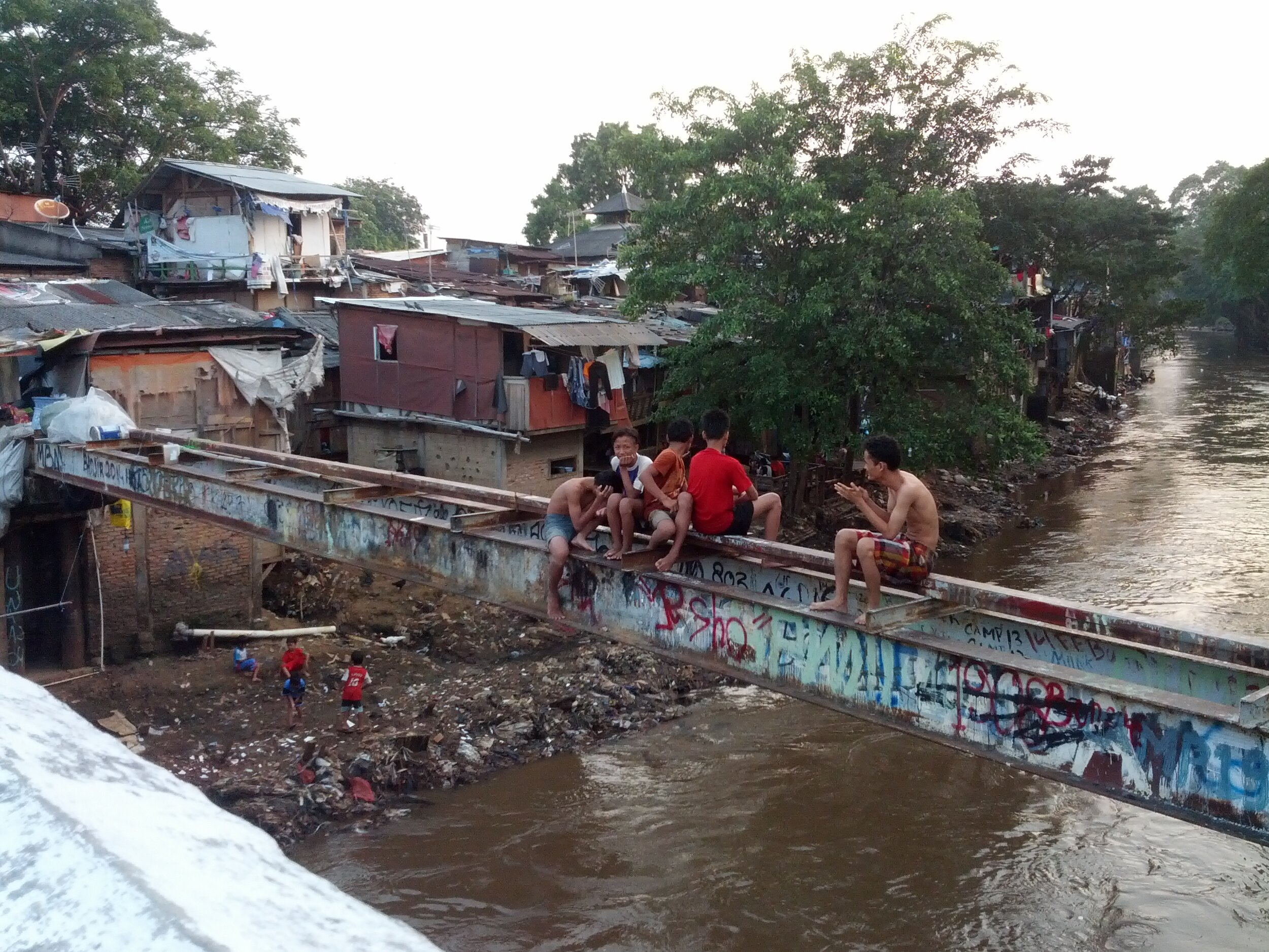 Figure 1. A view from a bridge across River Ciliwung at Kampung Pulo, 2015. In the kampungs, infrastructure is inadequate and buildings are constructed incrementally, not subject to building codes. This kampung was demolished in August 2015 to expand the capacity of the river. Photograph by Abidin Kusno.