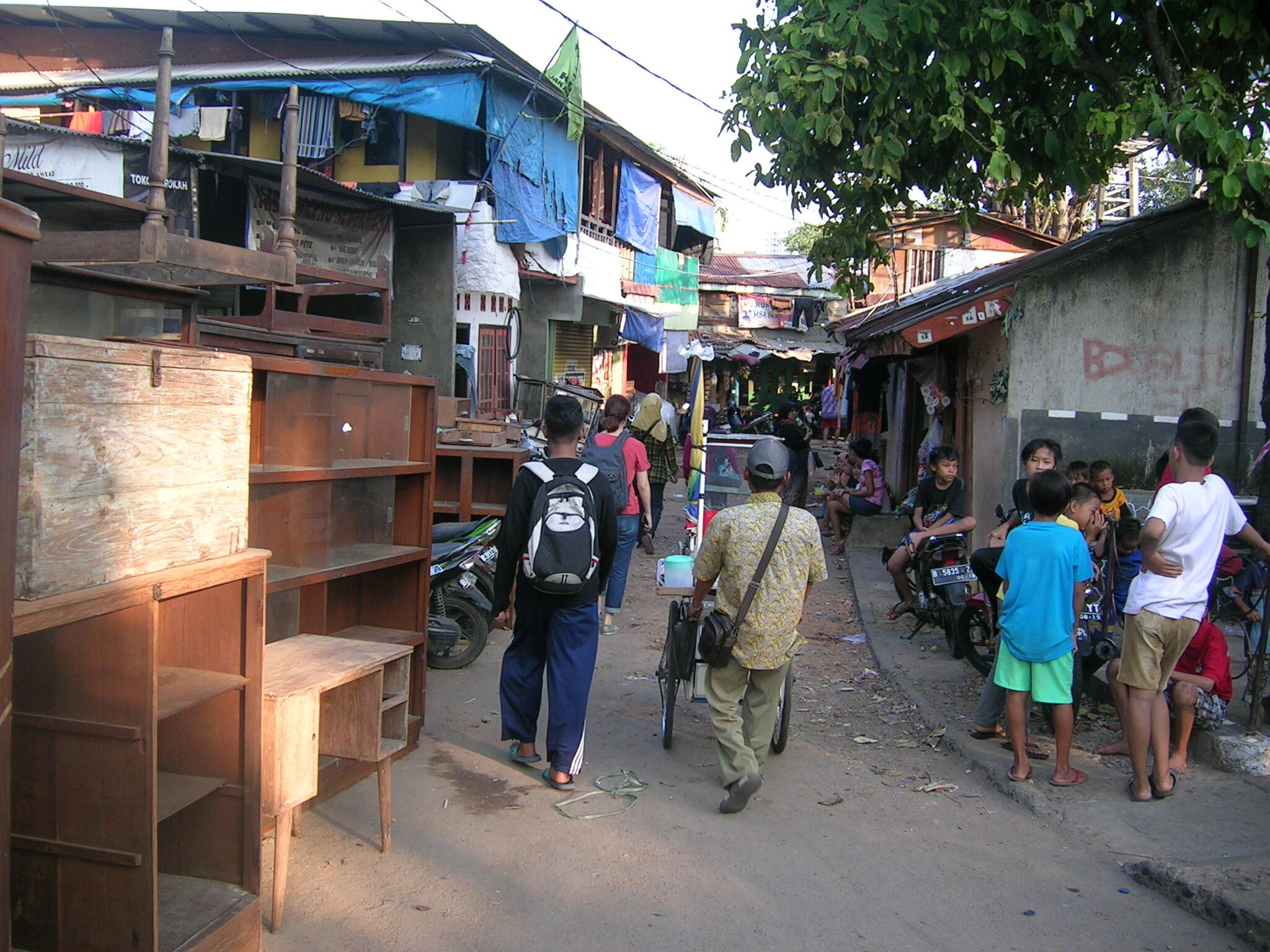 Figure 3. Kampung Pulo, 2015. This kampung, demolished shortly after this photograph was taken, played an important economic role as an income-pooling domain for workers. Like other kampungs in Jakarta, many of its households included one or two members who worked in the formal sector (such as in shopping malls, office buildings, or factories), while others earned a living as street vendors (such as the man at center) and maids, or in petty commodity production and retail, selling wares such as furniture. Photograph by Abidin Kusno.