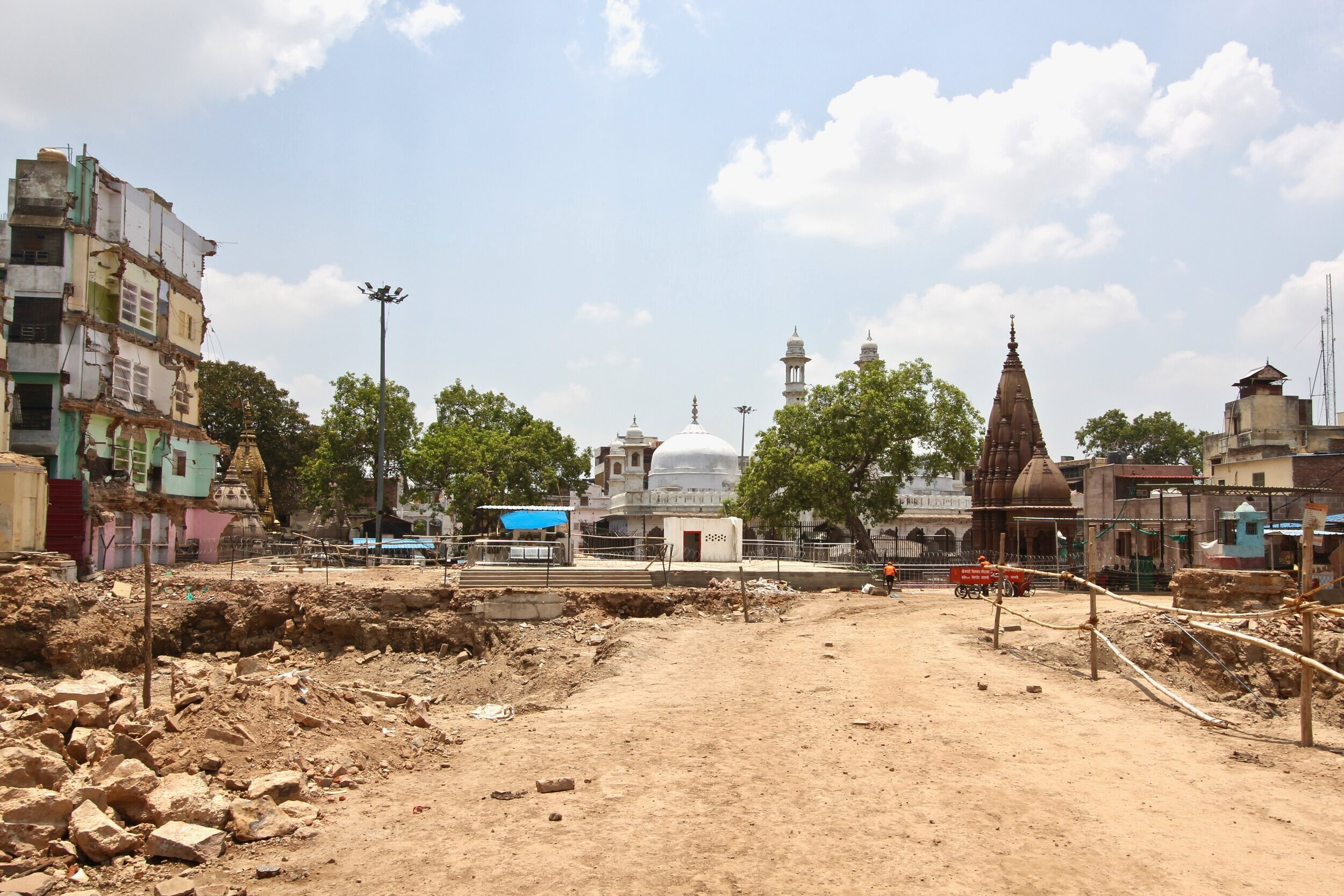 "Figure 17. The excavation of the Vishwanath Corridor also reveals a different historical structure—the  Gyanvapi Mosque , built by the Mughal emperor Alamgir (Aurangzeb) on the site of an earlier Hindu temple, ca 1669. The corridor, then, leads not just to the Kashi Vishwanath temple, but also to the mosque, which sit side-by-side, heavily guarded by Indian police and special forces. Many observers are concerned that the corridor is in fact just a pretense to facilitate the destruction of the mosque, as happened in Ayodhya in 1992. Indeed, the mosque's domes and minarets are now visible from multiple vantage points in a way that they were not before. A wall shared by the mosque and temple was demolished recently, causing great concern for the city's Muslim population. Some people have told me that they think this was a ""test"" to see what might happen if the mosque was threatened. Several men were also arrested attempting to bury a Hindu icon in the mosque precinct, in essence trying to claim for that space a Hindu historicity. Photograph by Michael S. Dodson, July 2019."