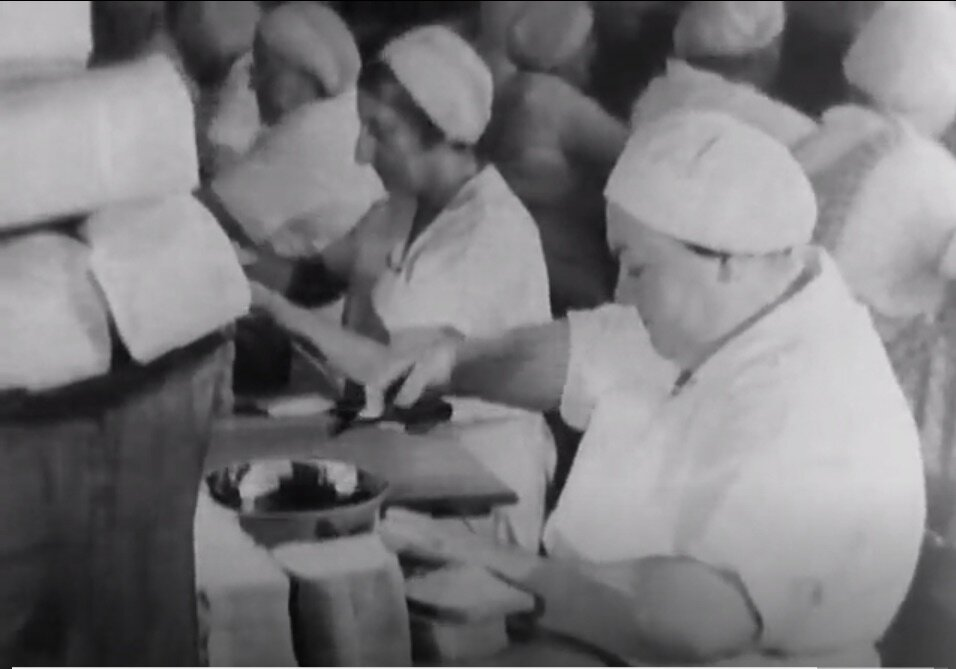 Screenshot 4. A woman making school lunches in an industrial kitchen.  A Better New York City , 1937, Federal Works Agency, Works Progress Administration, National Archives.