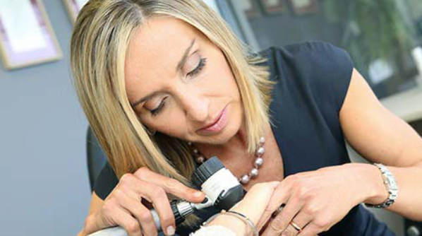Dr Nina Wines performing a skin check with a dermascope.