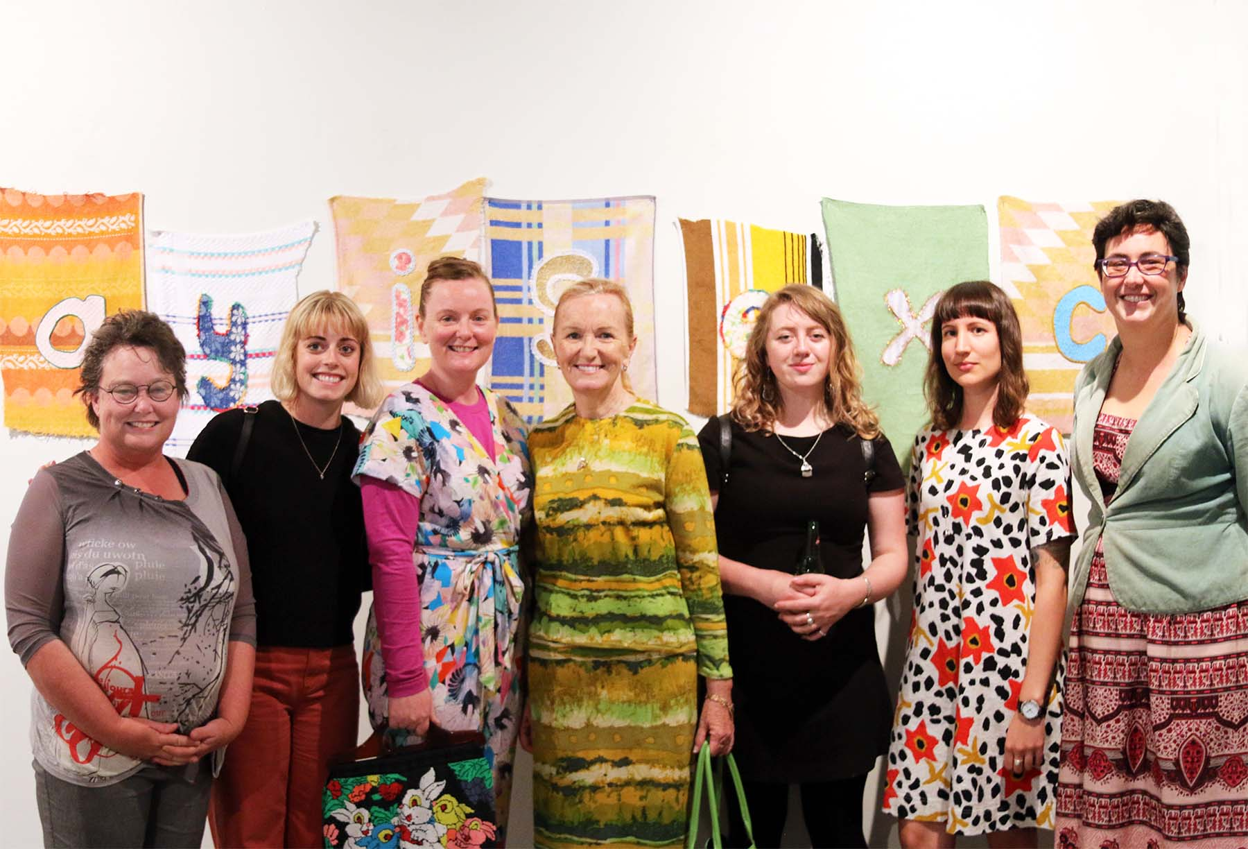 Left to Right : Amelia Rowe, Kathryn Camm, Mae Finlayson, Louise Parsons, Emma  Magnusson-Reid, Holly Leonardson, Karen Hall, in front of work by Mae  Finlayson.  Photography by Jo Pitchford