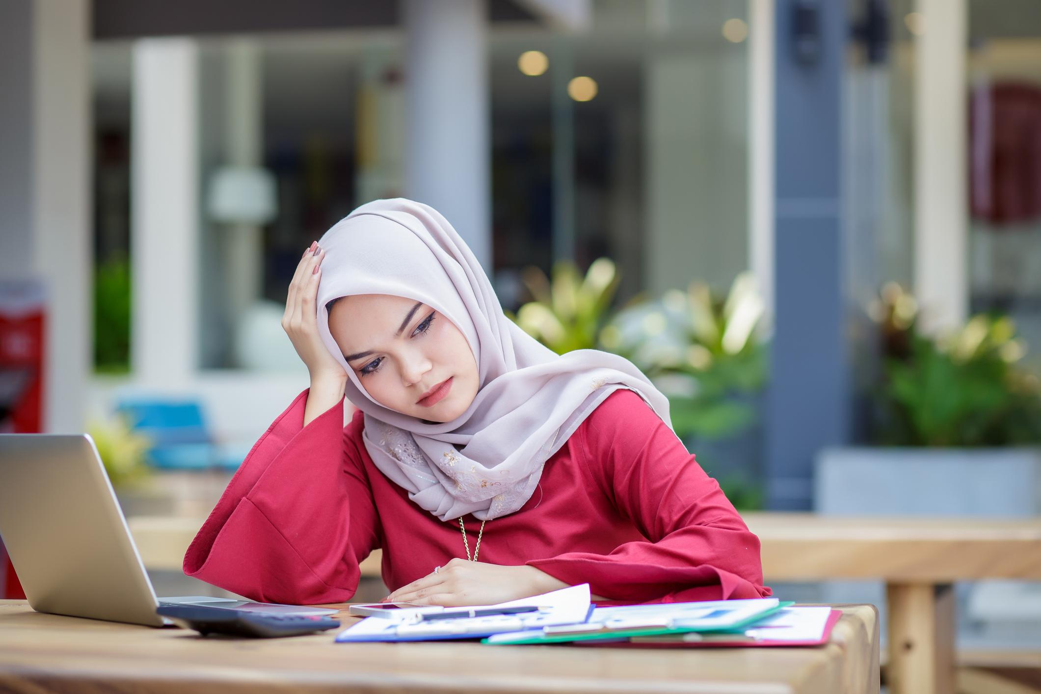 overwhelmed asian muslim woman stock photo.jpg