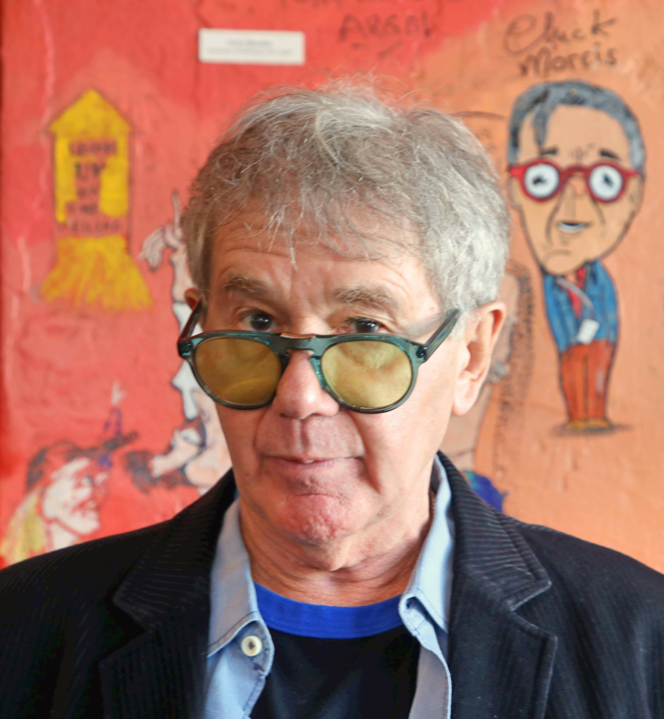 Chuck Morris poses in front of his caricature on the Wall of Fame. Photo Credit: Teresa Taylor