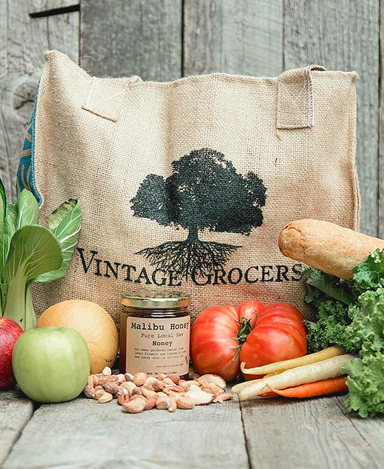 A picture of a Vintage Grocers bag with gourmet fruits, vegetables and treats from the market.