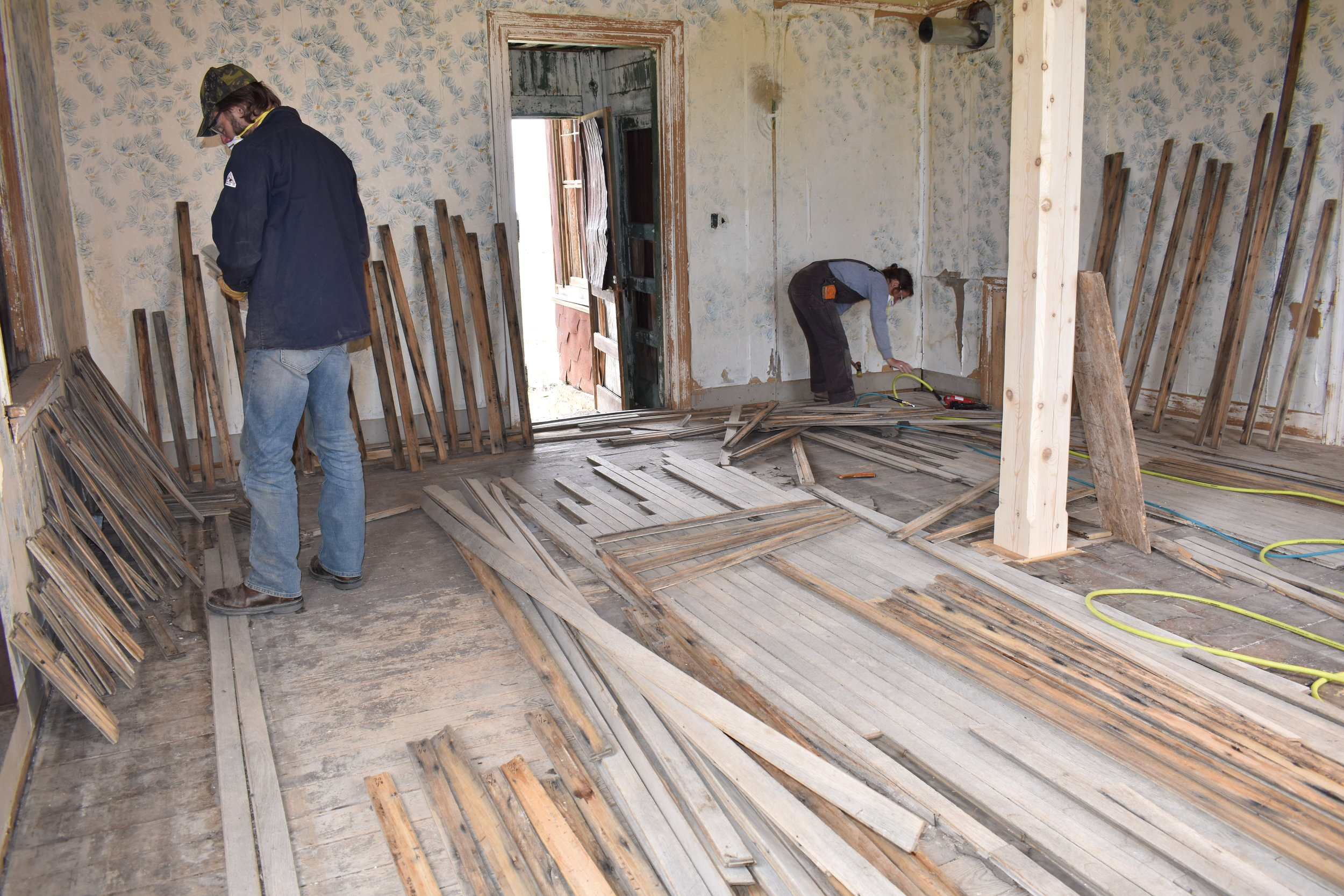 Molly Greenhouse and Todd Woolf of HistoriCorps work to repair on the original oak flooring inside the Bodie Railway office in 2019. Photo by Chris Spiller