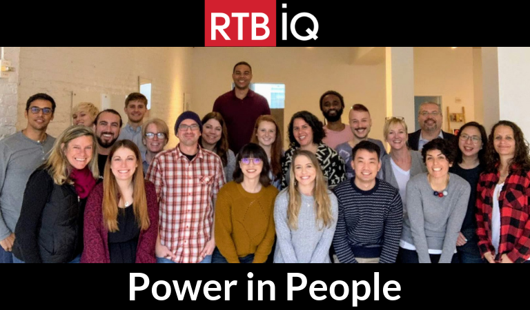 "Group photo of RTBiQ employees with text overlay ""RTBiQ Power in People"""