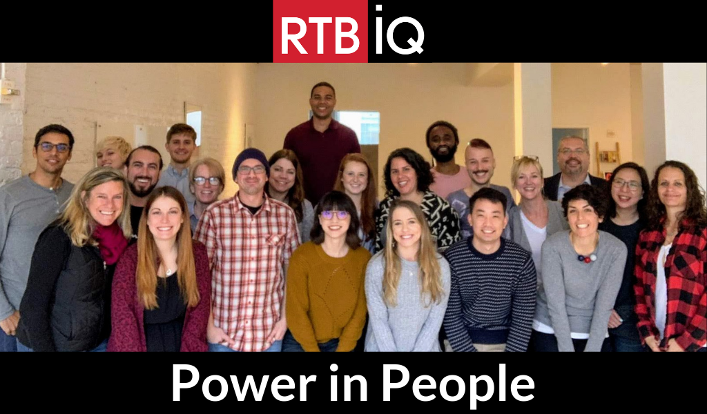 """Group photo of RTBiQ employees with text overlay """"RTBiQ Power in People"""""""