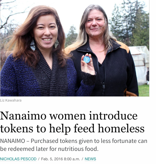 Nanaimo newspaper with Liz and Cheryl holding up the token. The headline reads Nanaimo women introduce tokens to help feed homeless by Nicholas Pescod