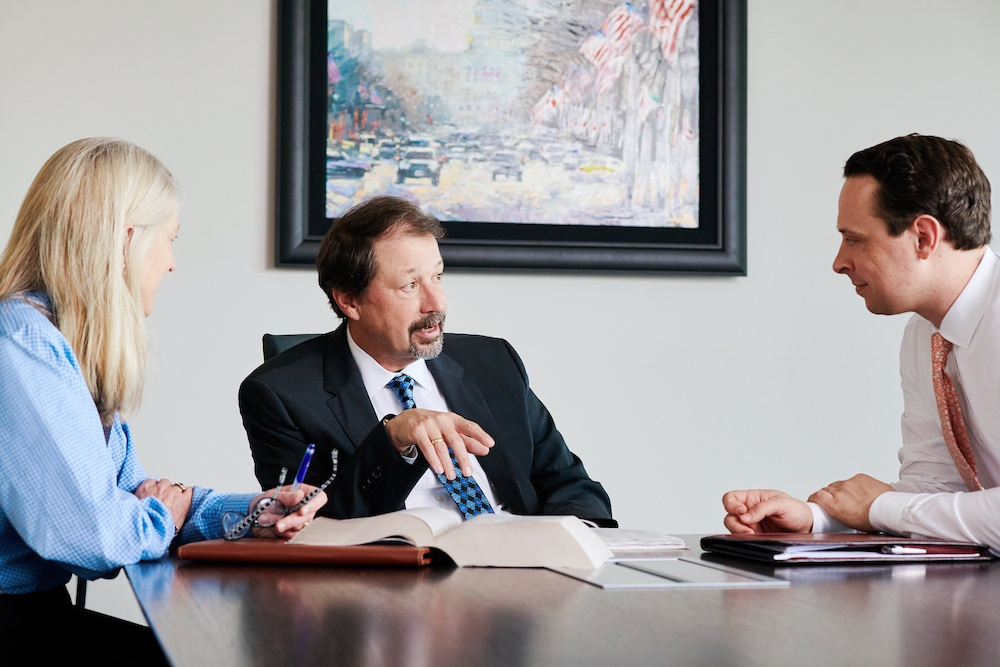 Capitol Tax Partners, Joe Mikrut, Annabelle Canning, and Jake Triolo, working on a case in a conference room.
