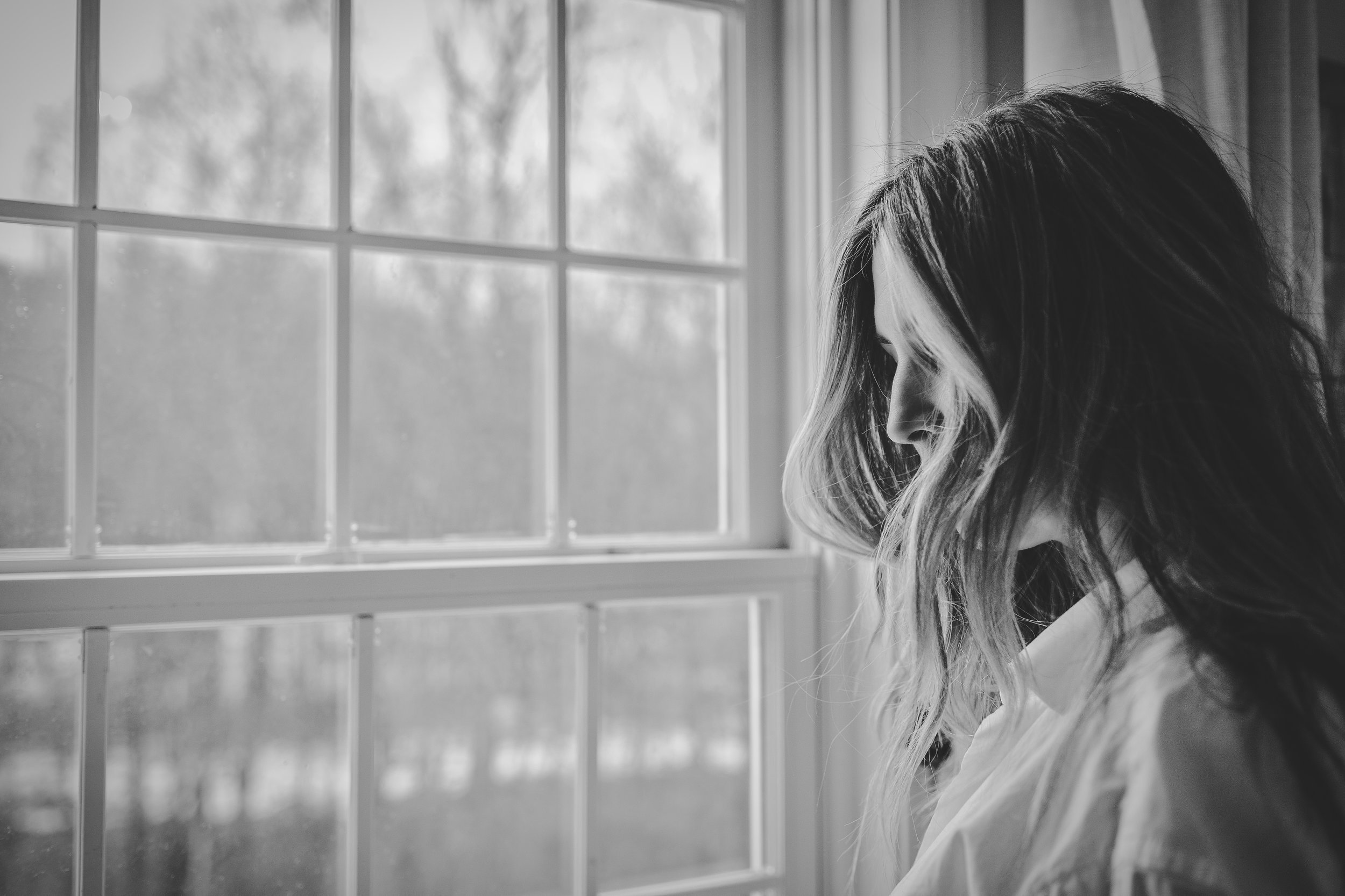 woman at window with stress and anxiety