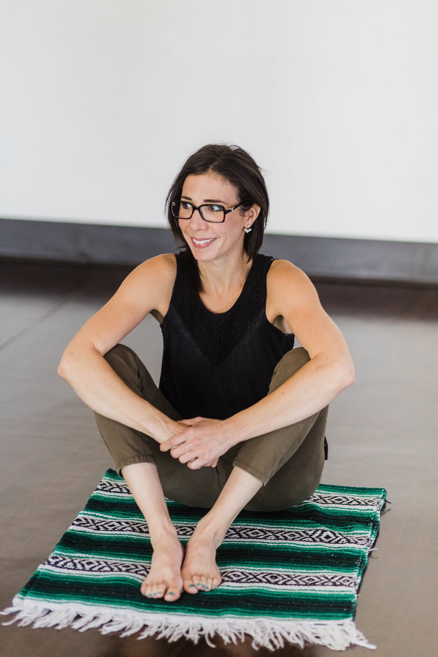 woman sitting on a yoga blanket in yoga studio.jpg
