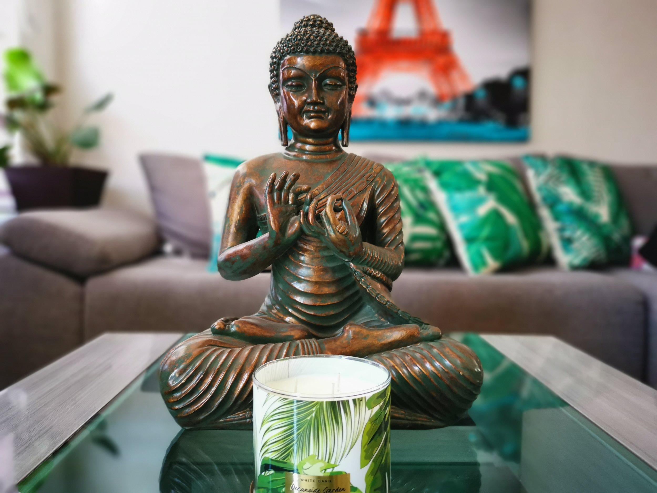 buddha meditating with candle