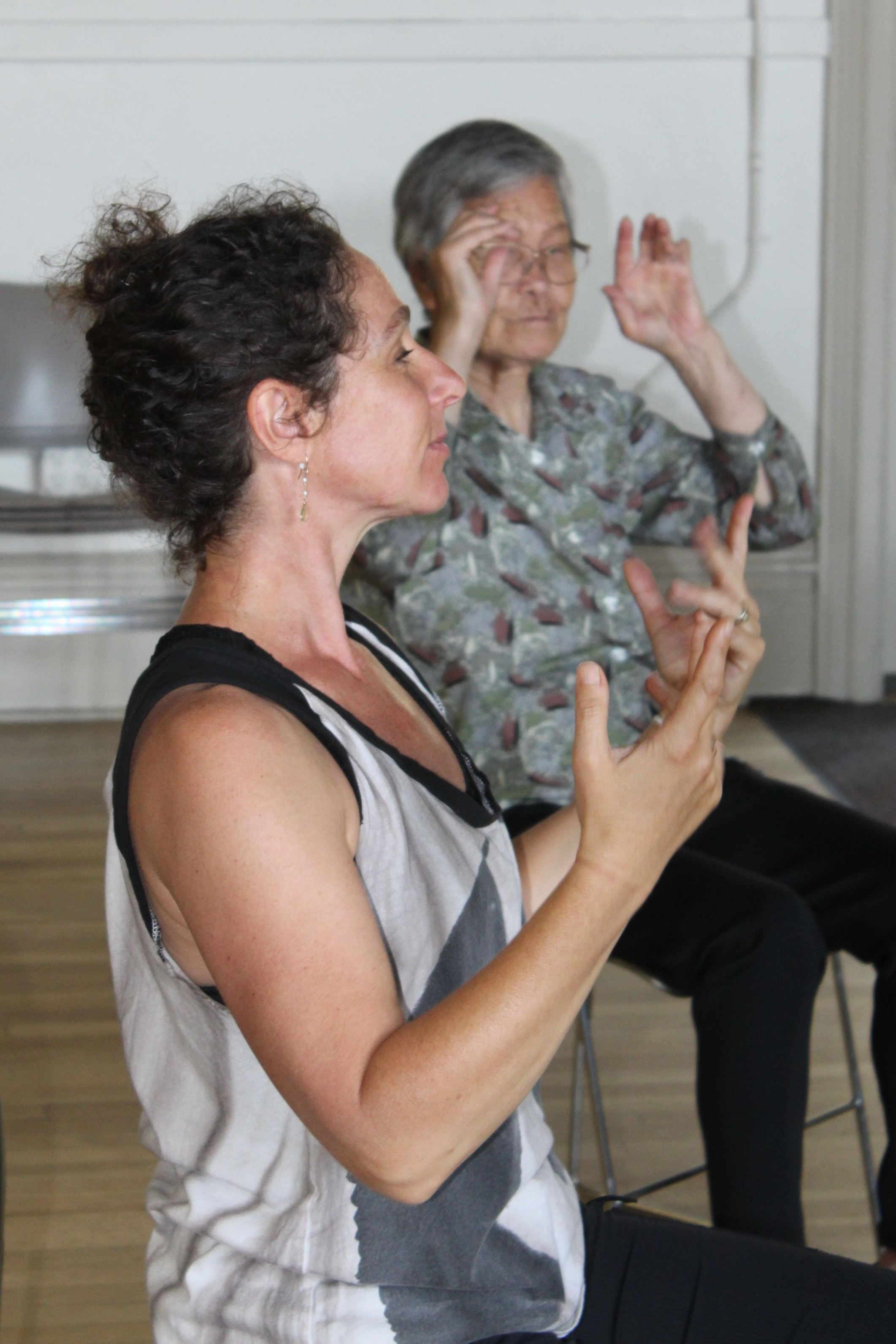 Instructor Marika Brussel and a class participant seated in chair during class.
