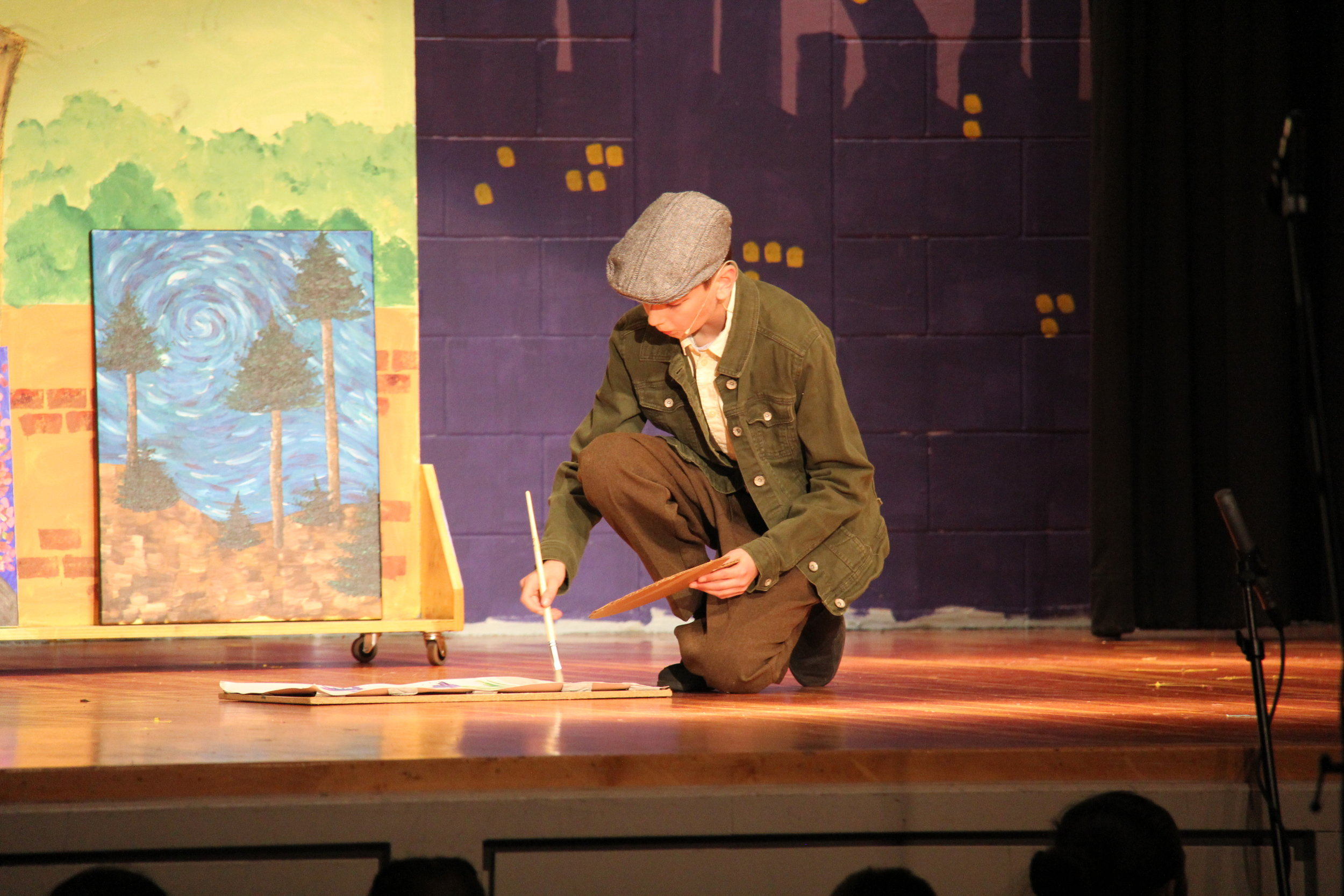 Student playing the role of a painter on-stage at the annual Immaculate Conception School drama performance.
