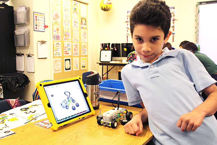 A UCP Downtown/BETA student poses with his robotics project.