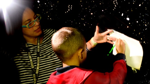 UCP Bailes Community Academy student learning constellations inside a homemade planetarium created by UCP's education team.