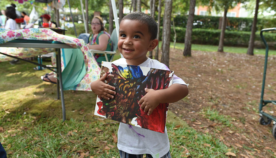 A young student proudly showing their masterpiece during a UCP Art Fair.