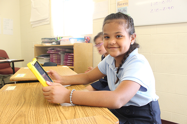 A UCP Downtown/BETA student using her iPad to interact with lesson plans.