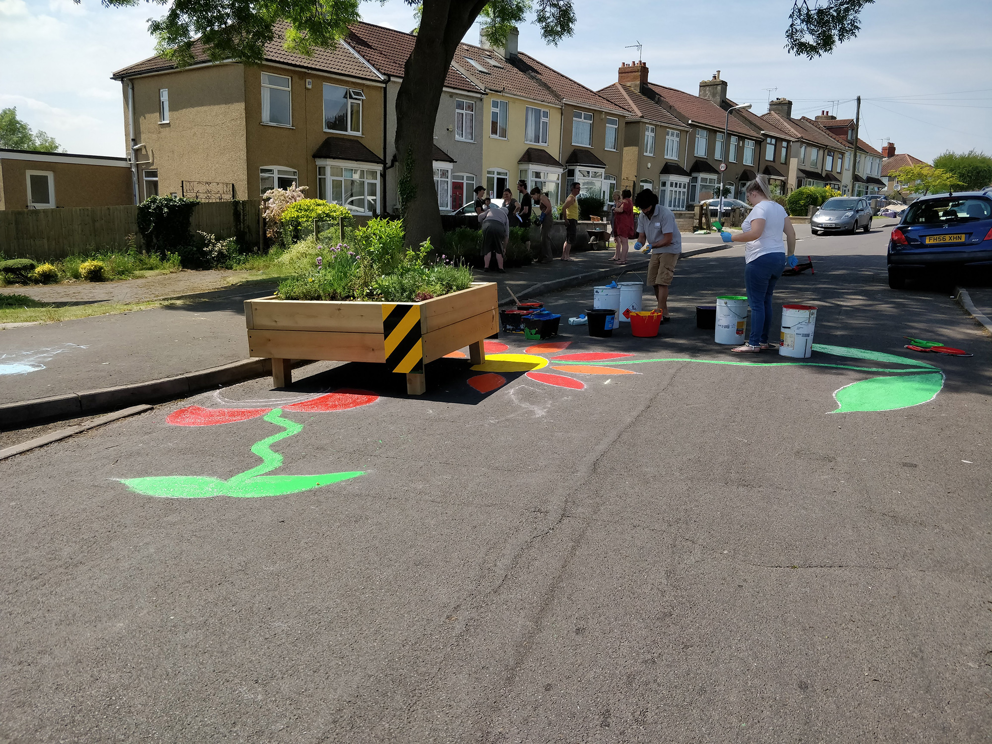 Painted coloured road markers highlighting the raised flower bed speed reducers