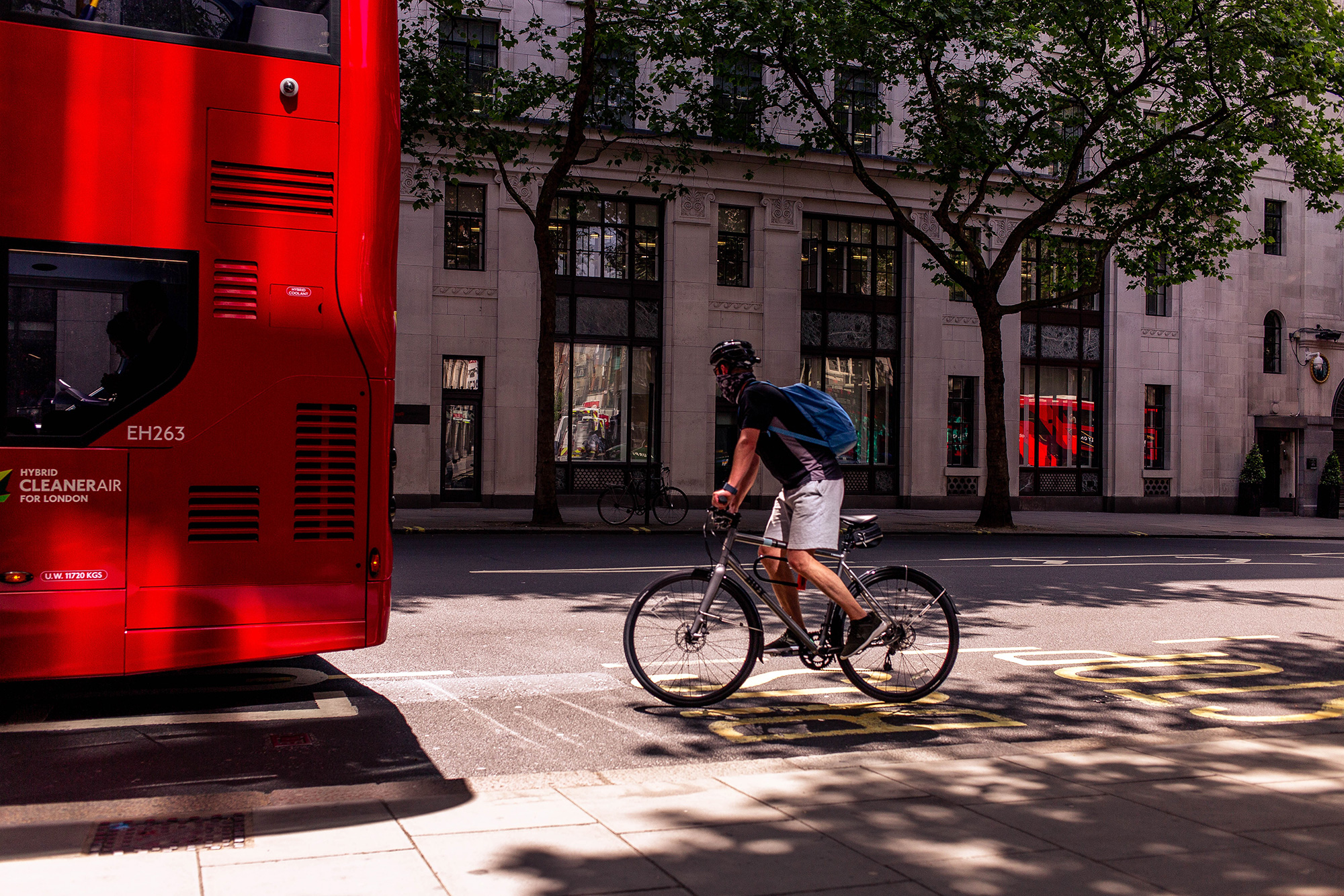 Cyclist riding behind a bus on a city street