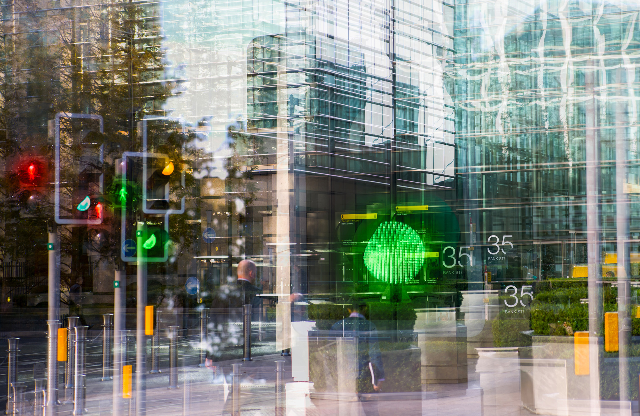 Traffic lights and pedestrians reflected in the windows of a city office building
